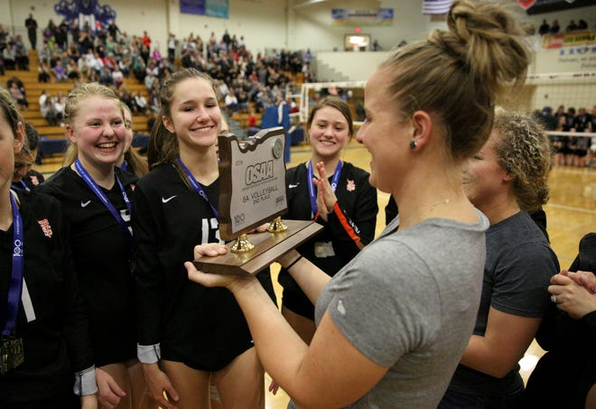 Sprague head coach Anne Olsen holds the second place state championship trophy following the OSAA 6A Volleyball State Championship on Saturday, Nov. 3, 2018 in Hillsboro.
