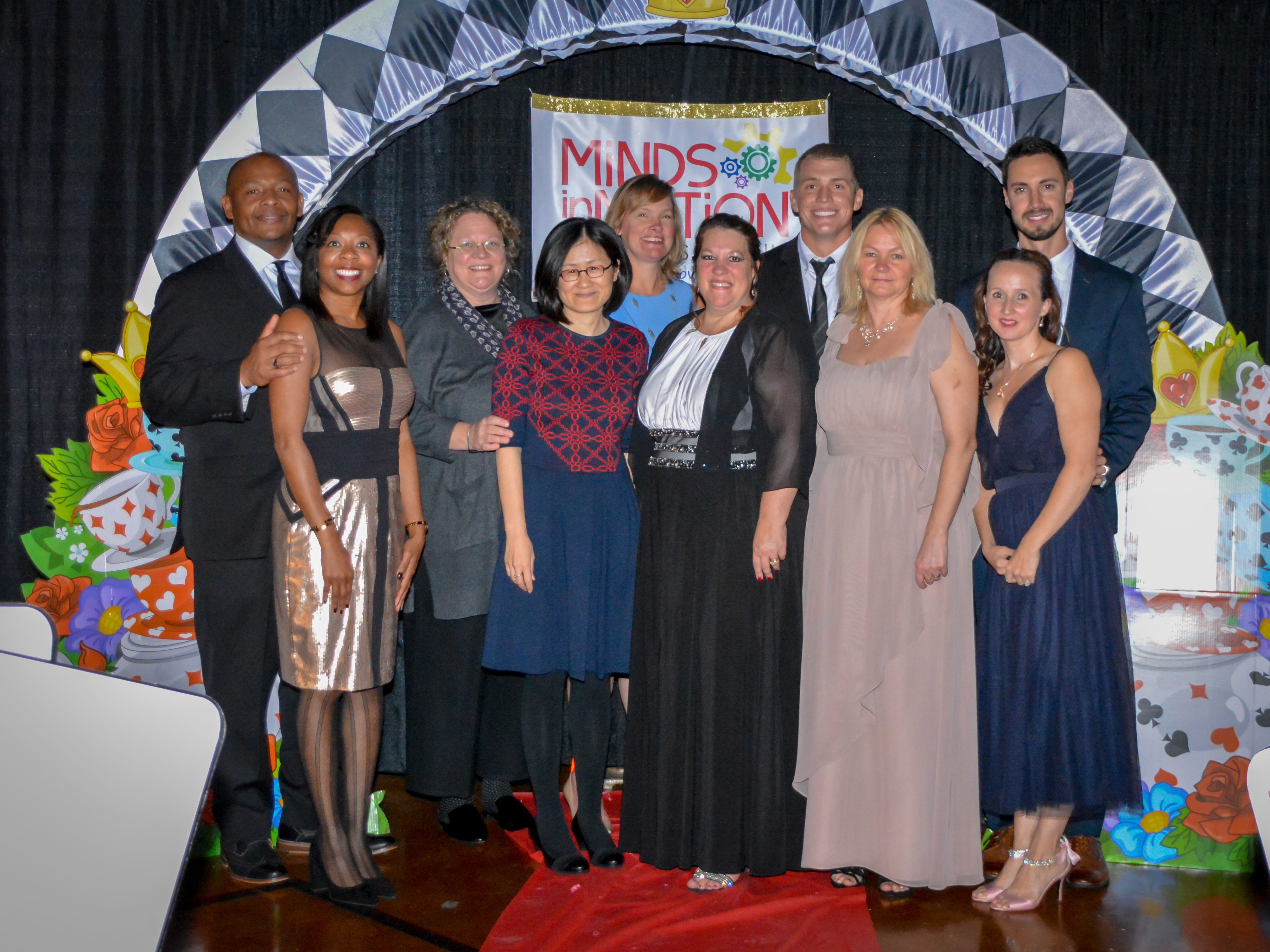 """Laurie Henry, Brandy Terrill, Claudia Burgess, Chin-Hsiu Chen, Vince Genareo, Kristen Maloney, Diallo Sessoms and Chalarra Sessoms, Eddie Daniels and Eva Bothazi take a group photo at the Minds in Motion Museum """"A Wonderland Adventure Gala"""" on Nov. 3, 2018 at the Wicomico Youth & Civic Center in Salisbury, Maryland."""