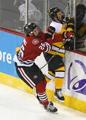 St. Cloud State's Easton Brodzinski (26) check a Colorado College player into the boards in the first period Saturday at Broadmoor World Arena in Colorado Springs, Colo.