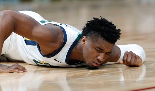 Utah Jazz guard Donovan Mitchell reacts after being injured during the second half of the team's NBA basketball game against the Denver Nuggets on Saturday, Nov. 3, 2018, in Denver. Mitchell was helped off the court but returned to the game in the fourth quarter. The Nuggets won 103-88.