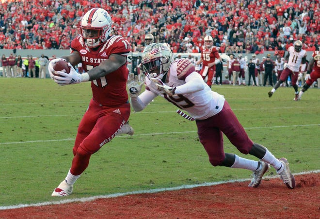 North Carolina State Wolfpack wide receiver Jakobi Meyers (11) scores a touchdown defended by Florida State Seminoles defensive back A.J. Westbrook (19) during the second half at Carter-Finley Stadium.
