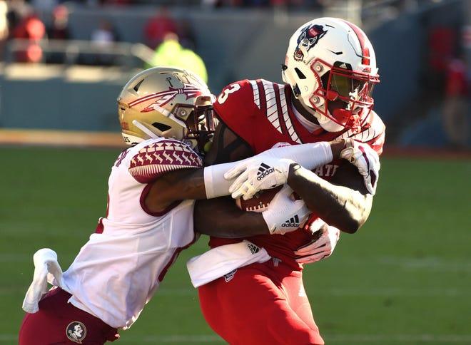 FSU defensive back Stanford Samuels III tackles N.C. State wide receiver Kelvin Harmon in the Wolfpack's 47-28 win.