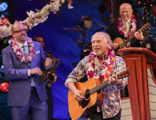"""FILE - In this March 15, 2018 file photo, Jimmy Buffett, center, members of the cast and production team are seen during the curtain call following the Broadway opening night of """"Escape to Margaritaville"""" at the Marquis Theatre in New York. President Donald Trump and Buffett faced off as the Florida Senate and gubernatorial races hit the final weekend of campaigning. Democratic incumbent Sen. Bill Nelson and the party's gubernatorial candidate, Tallahassee Mayor Andrew Gillum, appeared Saturday, Nov. 3, 2018, at a free West Palm Beach concert with laidback singer Buffett before more than 1,000 people. (Photo by Brent N. Clarke/Invision/AP, File)"""