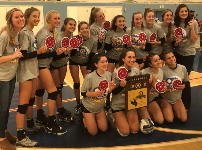 The Grace Brethren girls volleyball team poses with the championship plaque and patches after winning the Division 6 title on Saturday night.