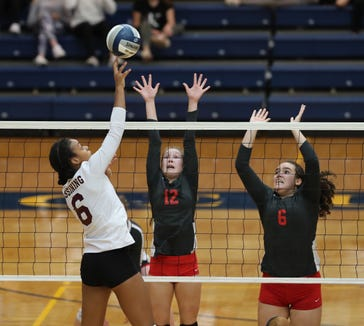 Ossining's Mychael Vernon (6) puts a shot past North Rockland's Emily Garvey (12) and Naomi Castillo (6) during their 3-2 win over North Rockland in the girls class AA volleyball section title game at Pace University in Pleasantville on Sunday, November 4, 2018.
