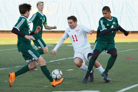 Somers midfielder Jon Riina beats a pair of Cornwall defenders to the ball in the first half of the Tuskers 5-0 win.