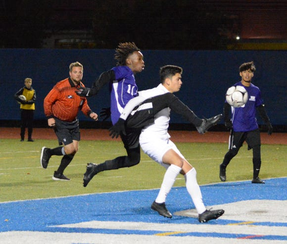 Indians midfielder John Mezza attempts to hold off Monroe-Woodbury forard Ikiel Collins-Brown in the second half of Saturday's regional final.