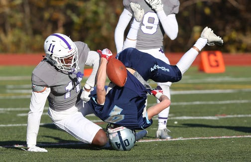 New Rochelle's Khairi Manns (11) tackles John Jay's Matt Beal (4) after a catch during the Section 1 championship game at Mahopac High School Nov. 3,  2018.