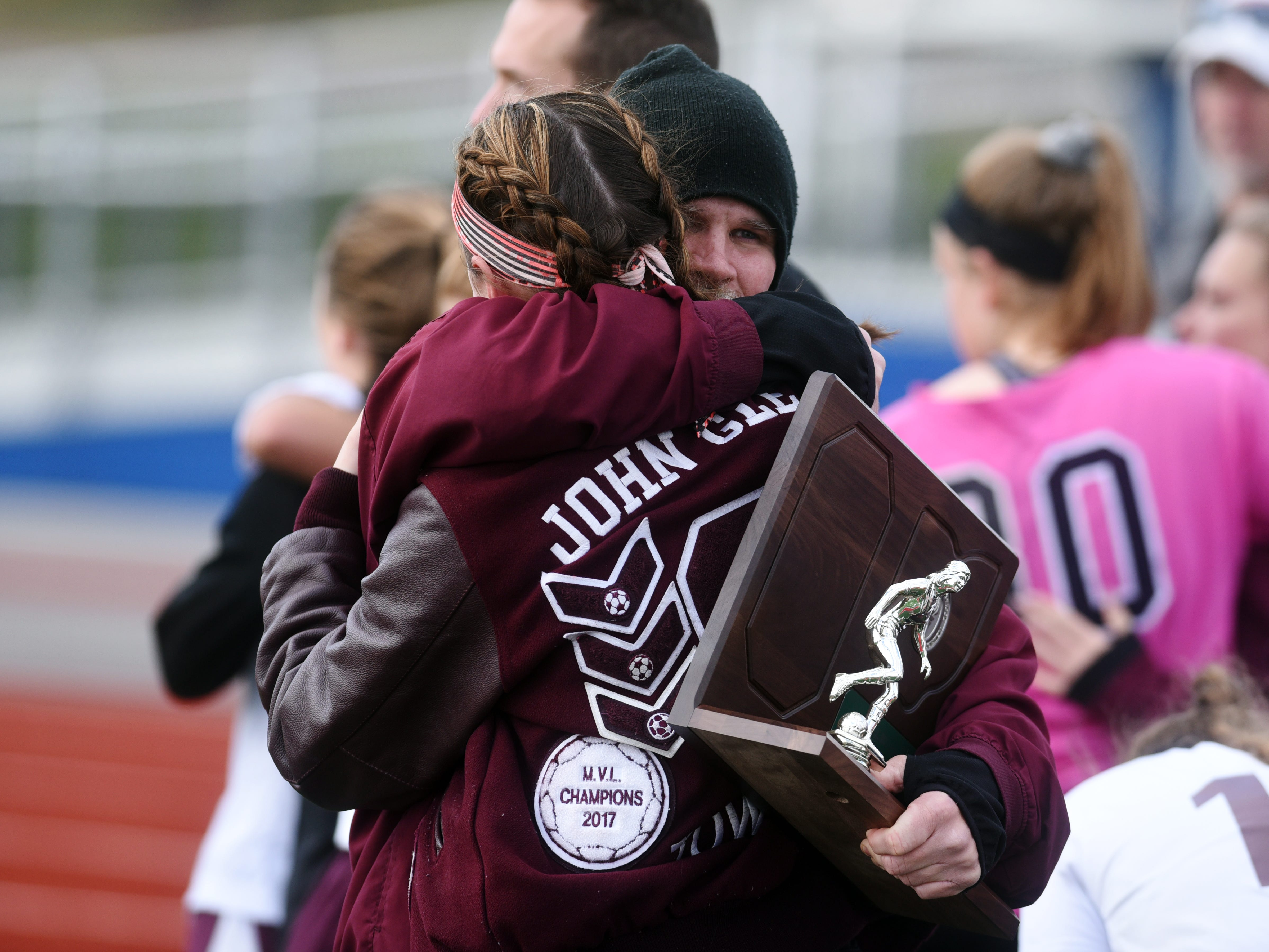 John Glenn girls soccer coach Clay Wilkins hugs one of his players following a 3-0 loss to Big Walnut on Saturday in a Division II regional final match at Lakewood High School.