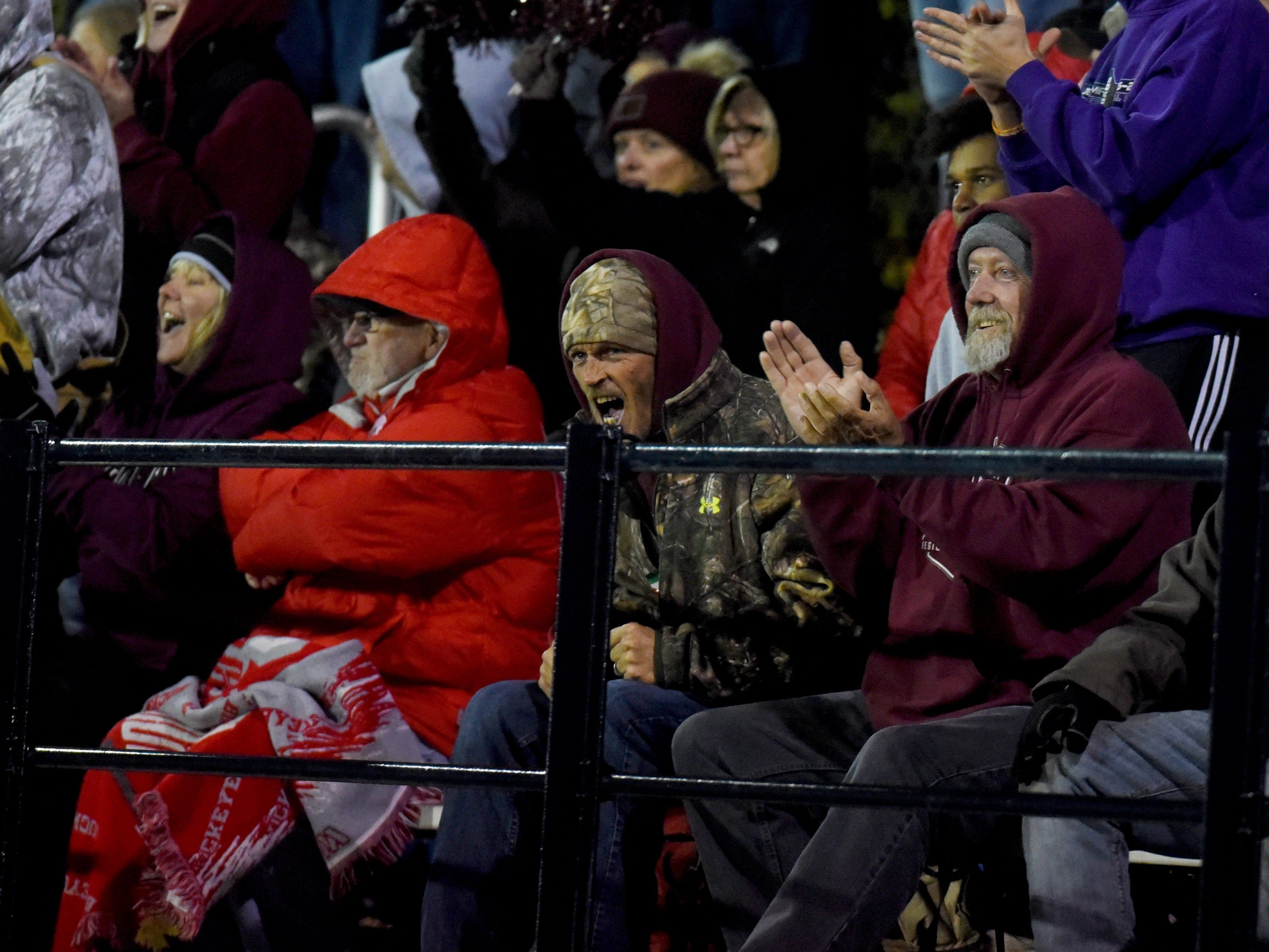 Fans cheer on the team during John Glenn's 16-14 playoff loss to host Gnadenhutten Indian Valley on Saturday night.
