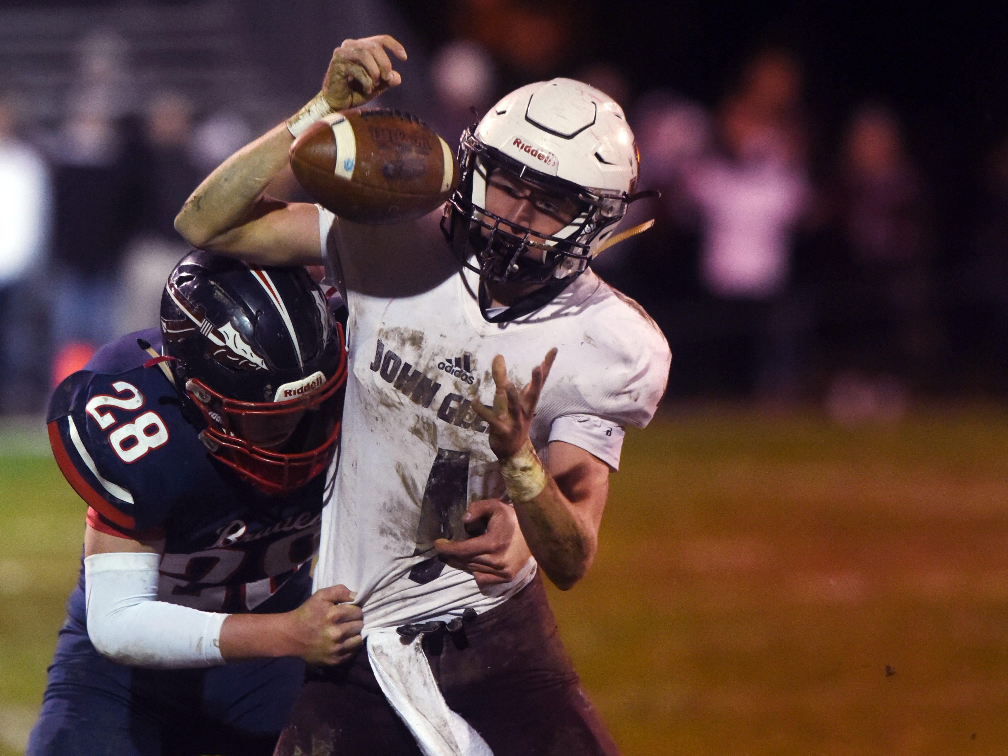 Parker Zachrich has the ball knocked loose by Kent Shupbach during John Glenn's 16-14 playoff loss to host Gnadenhutten Indian Valley on Saturday night.