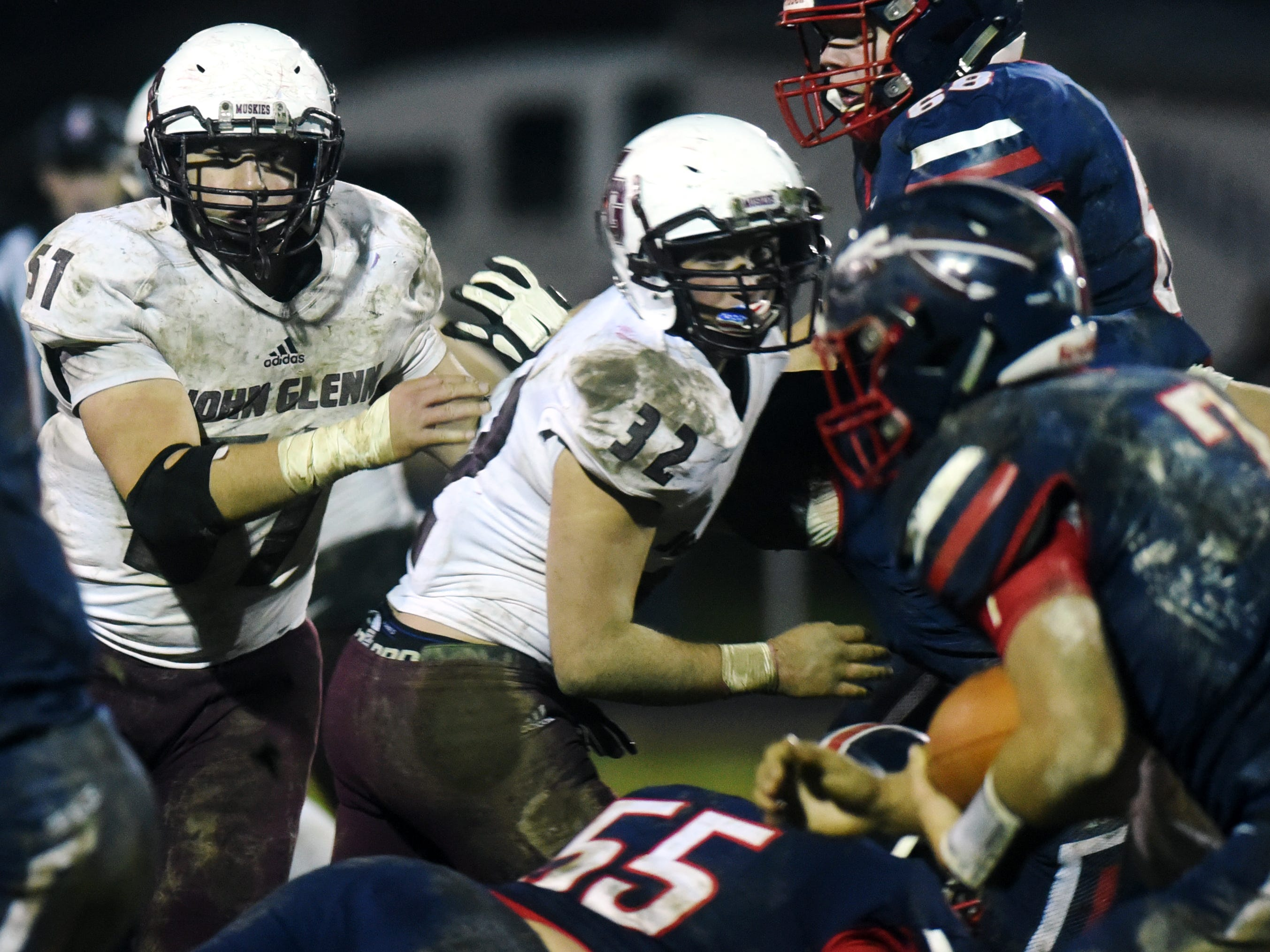 Linebackers Blaize Baker, left, and Eric Stillion size up Cade Williams during John Glenn's 16-14 playoff loss to host Gnadenhutten Indian Valley on Saturday night.