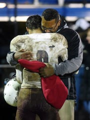 Joseph Clifford receives a hug from his dad following John Glenn's 16-14 playoff loss to host Gnadenhutten Indian Valley on Saturday night. Clifford played his final game, leaving as one of the most explosive players in program history.