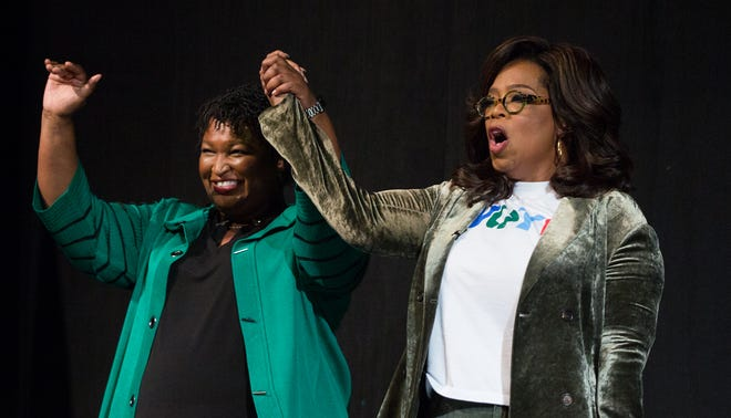 Oprah Winfrey and Georgia Democratic Gubernatorial candidate Stacey Abrams greet the audience during a town hall style event at the Cobb Civic Center on Nov. 1, 2018 in Marietta, Georgia.
