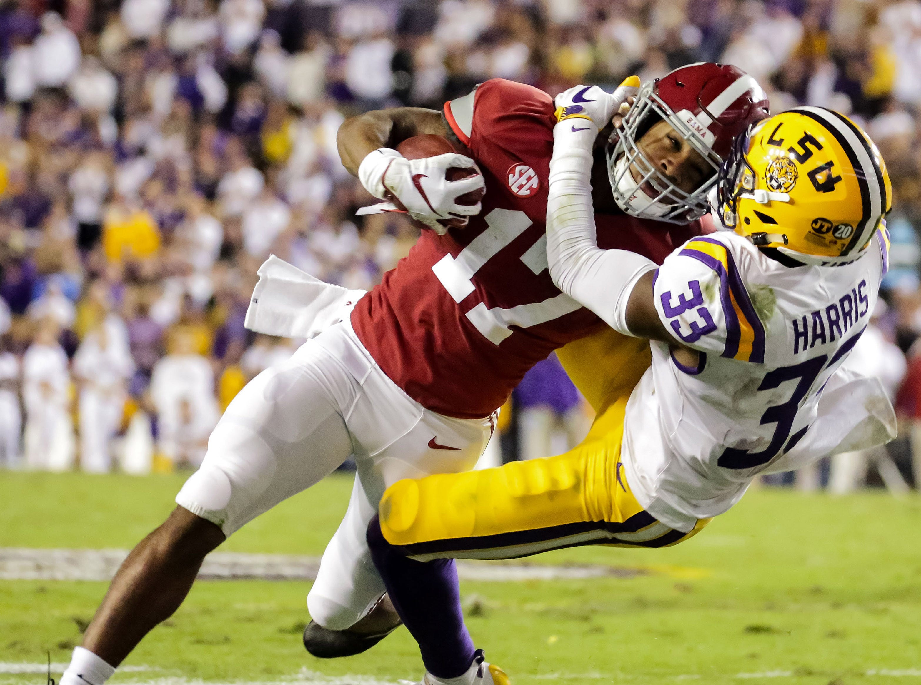 Alabama Crimson Tide wide receiver Jaylen Waddle (17) carries the ball as LSU Tigers safety Todd Harris Jr. (33) tackles during the second quarter at Tiger Stadium.