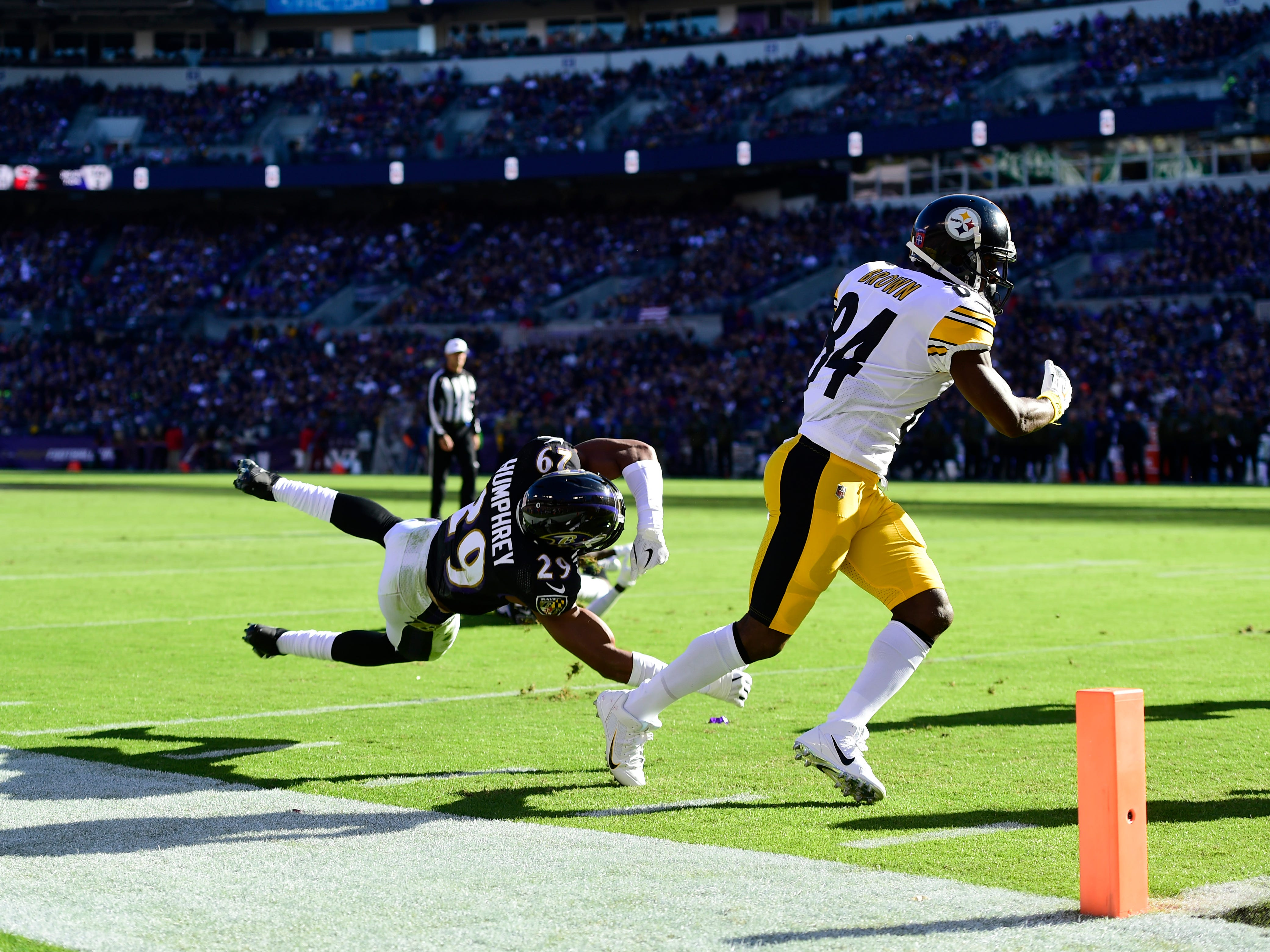 Pittsburgh Steelers wide receiver Antonio Brown (84) scoots runs past Baltimore Ravens cornerback Marlon Humphrey (29) for  a second-quarter touchdown at M&T Bank Stadium.