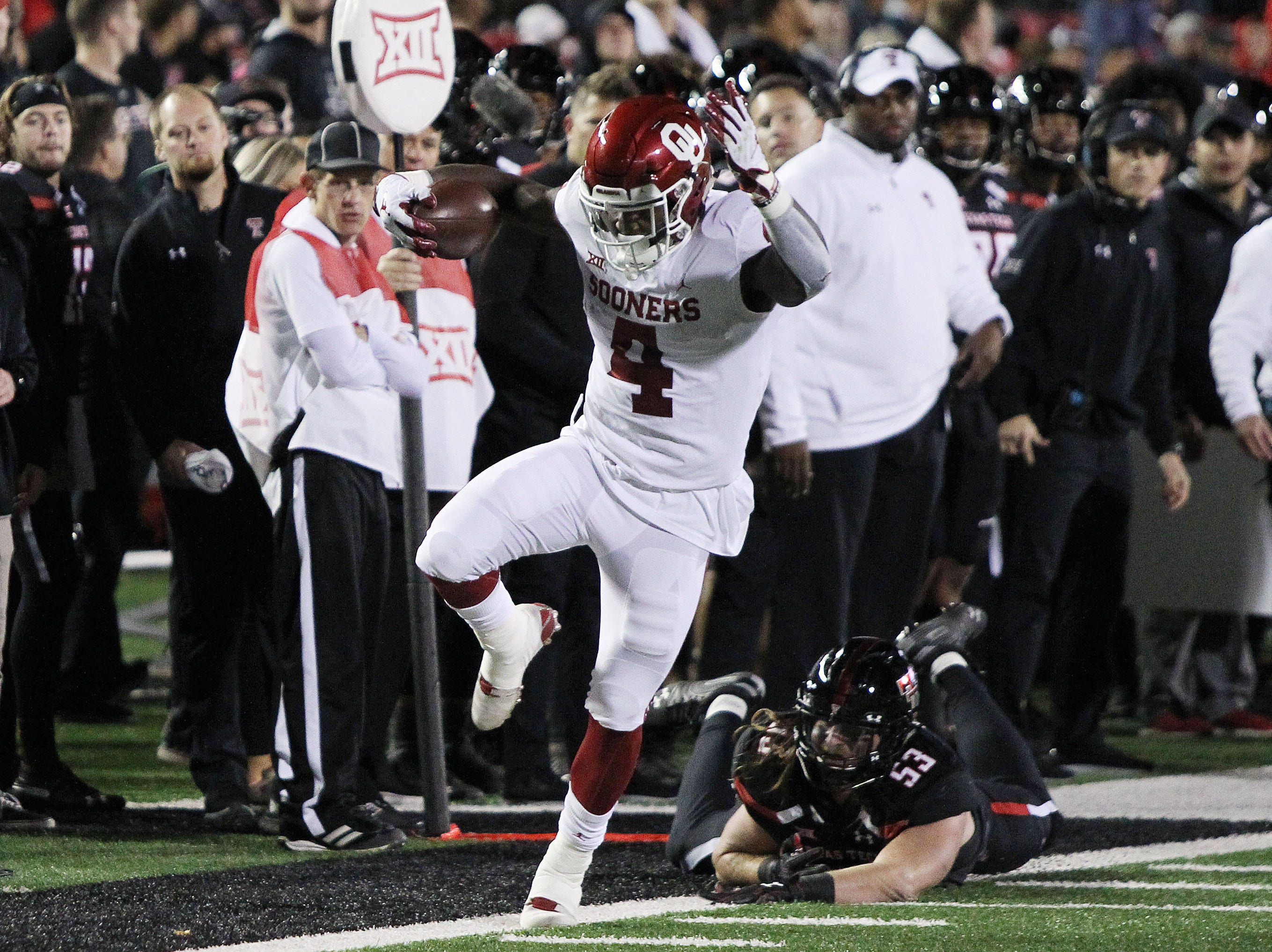Oklahoma Sooners running back Trey Sermon (4) scores a touchdown in front of Texas Tech Red Raiders defensive end Eli Howard (53) in the first half at Jones AT&T Stadium.