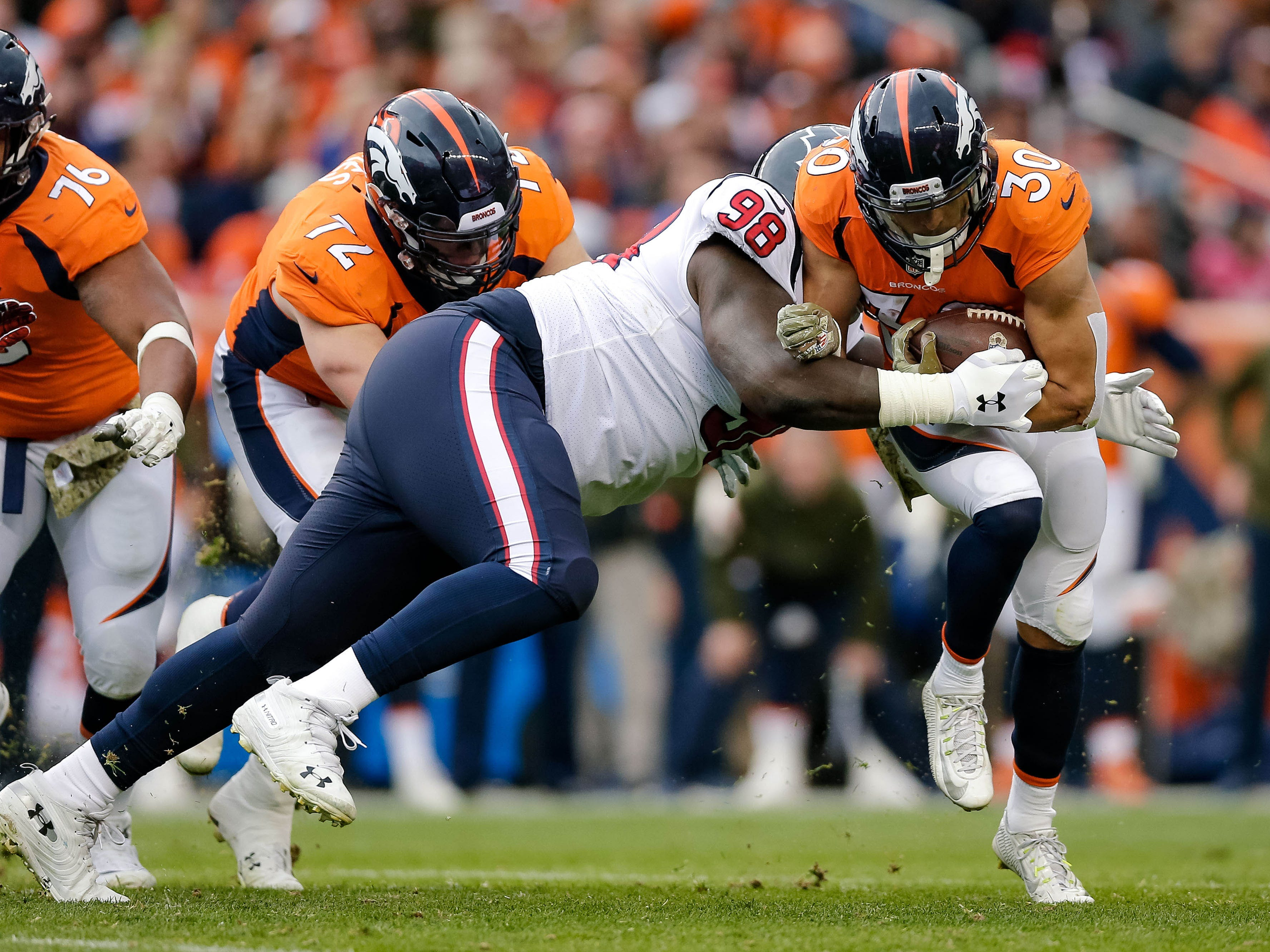 Houston Texans defensive end D.J. Reader (98) tackles Denver Broncos running back Phillip Lindsay (30) in the first quarter at Broncos Stadium at Mile High.