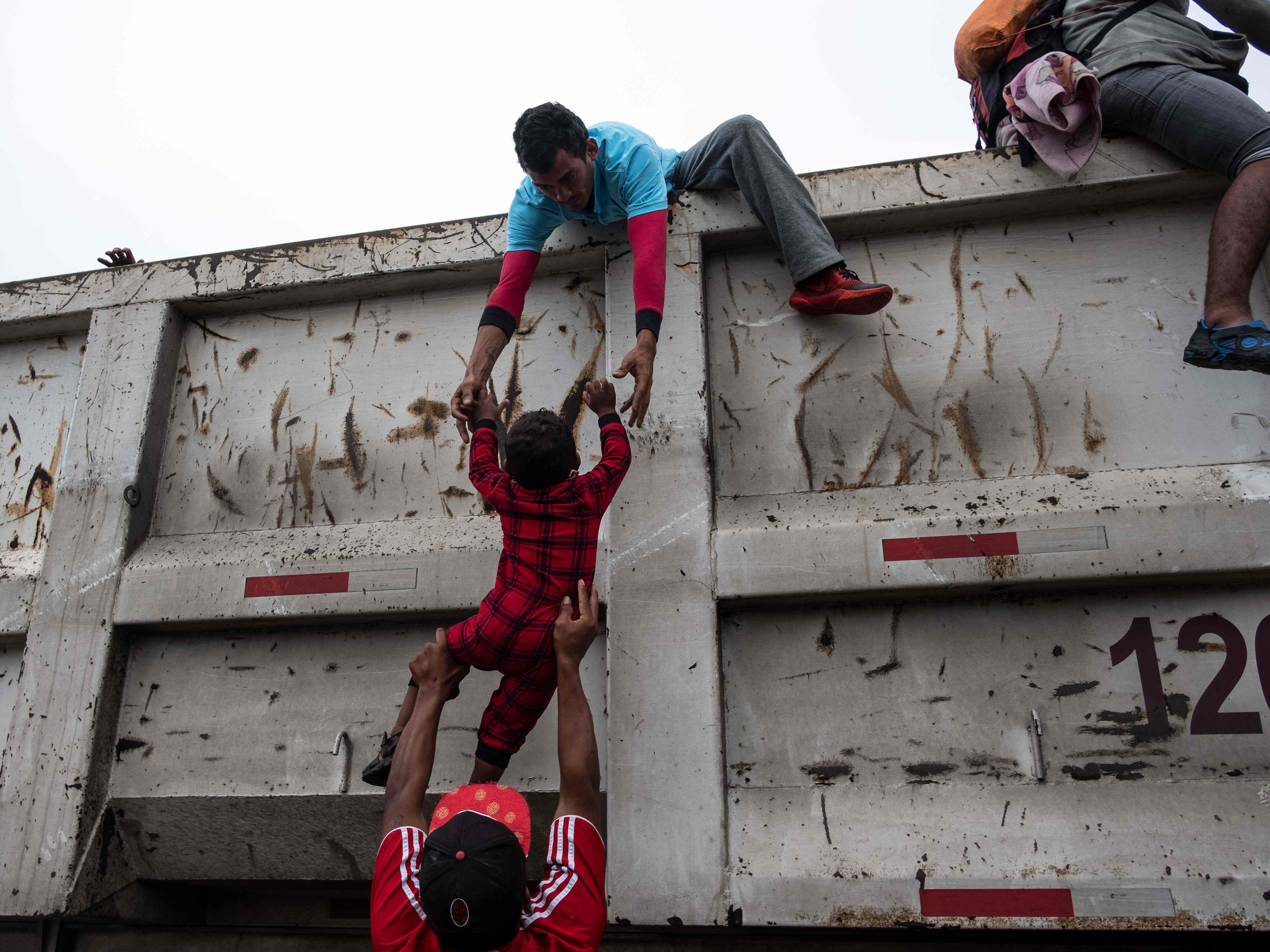 Migrants heading in a caravan to the U.S., help a child catch a ride on a truck on the road linking Sayula de Aleman and Isla, Veracruz state, Mexico, on Nov. 3, 2018.