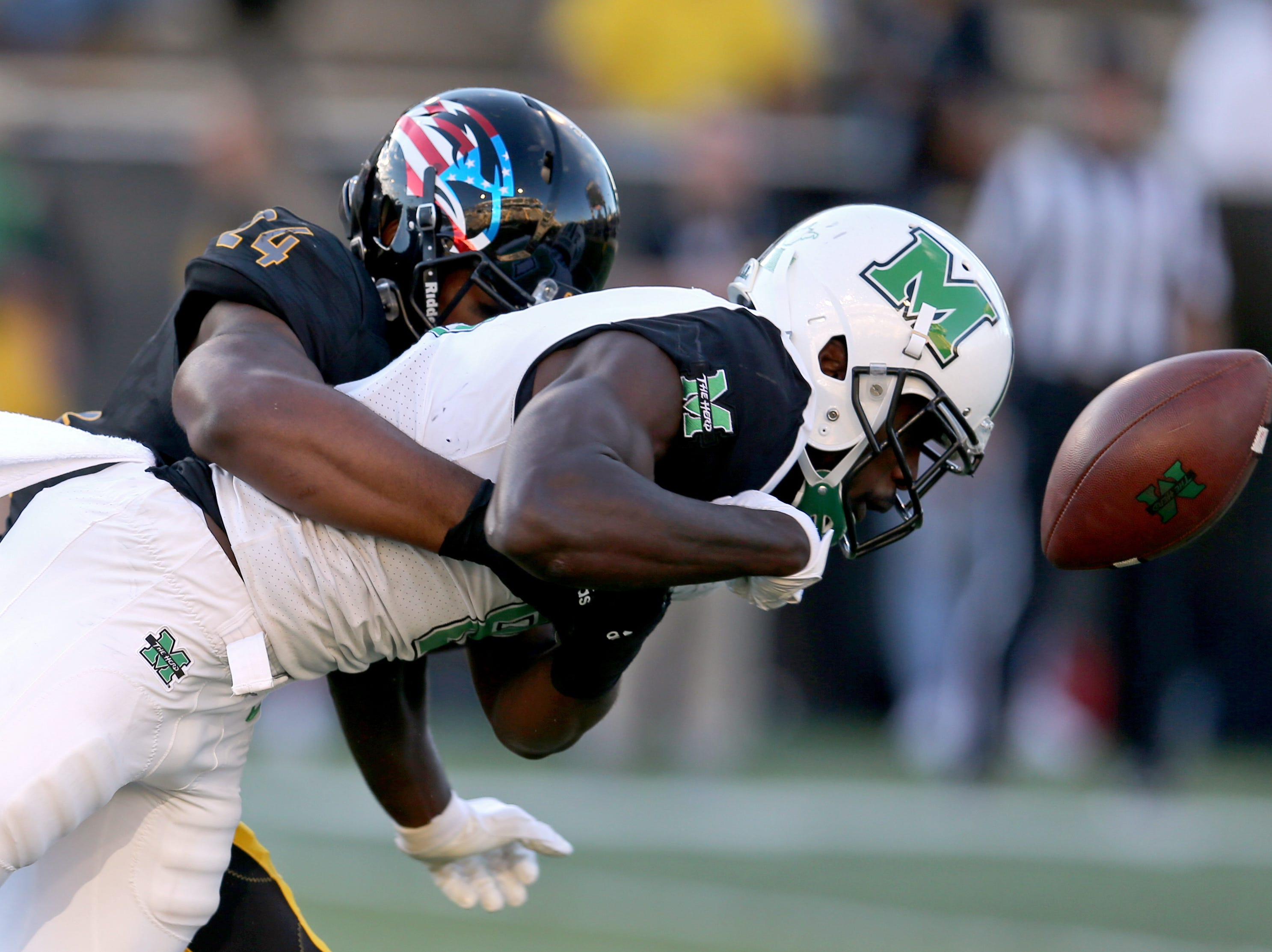 Marshall Thundering Herd wide receiver Tyre Brady (8) fumbles after a catch when hit by Southern Miss Golden Eagles linebacker Darius Kennedy (24) in the second half at M. M. Roberts Stadium.