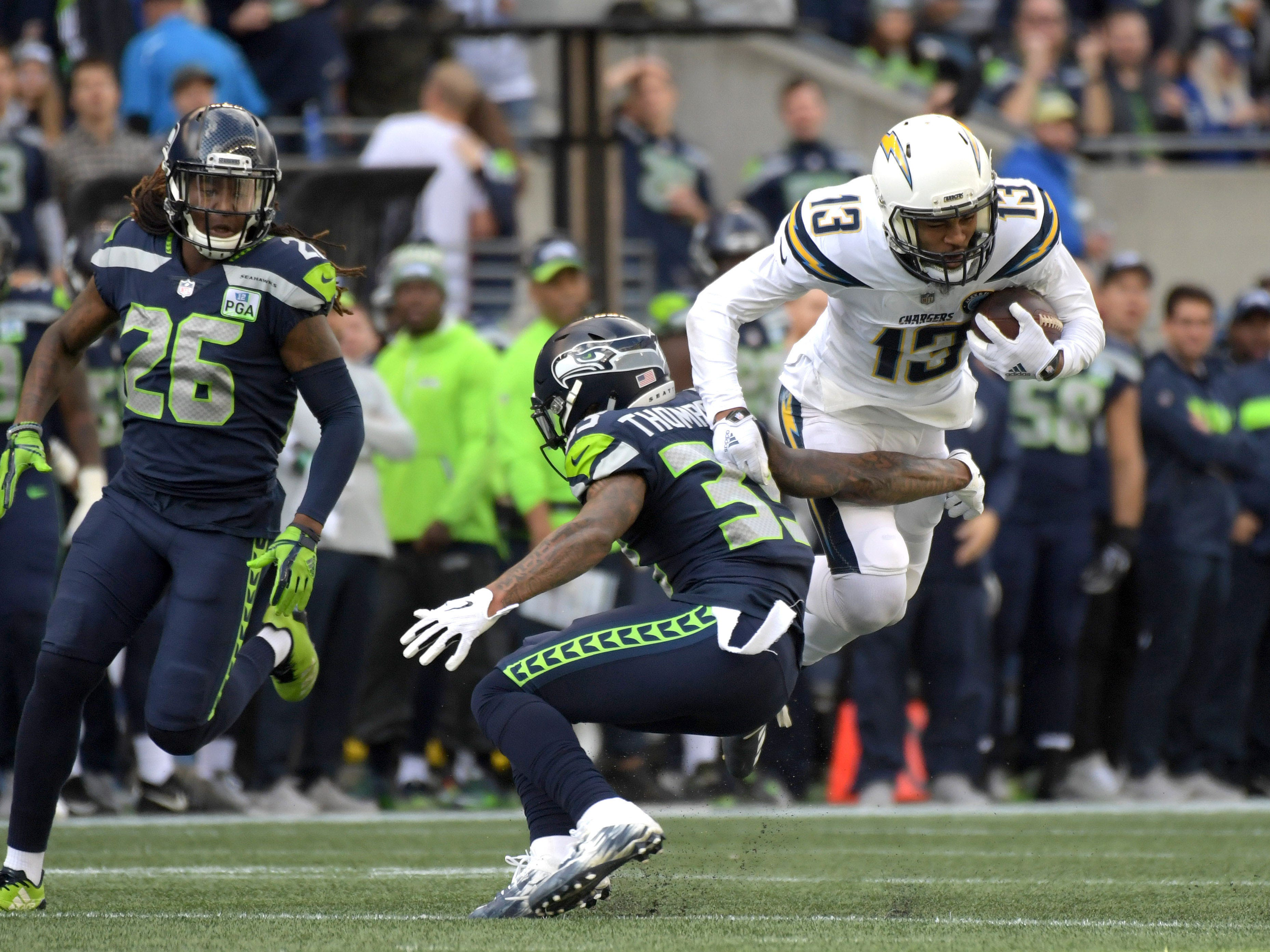 Seattle Seahawks defensive back Tedric Thompson (33) gets an arm out to trip up Los Angeles Chargers wide receiver Keenan Allen (13) in the second quarter at CenturyLink Field.