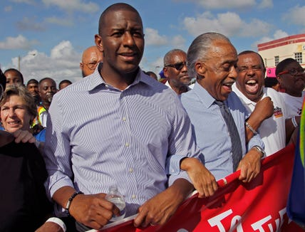 """Florida Democratic gubernatorial candidate Andrew Gillum, left, marches to the Caleb Center arm-locked with Rev. Al Sharpton, second from the left, and local politicians and supporters, as part of the """"Souls to the Polls"""" one of many events prior to the elections on Sunday, Nov. 4, 2018."""