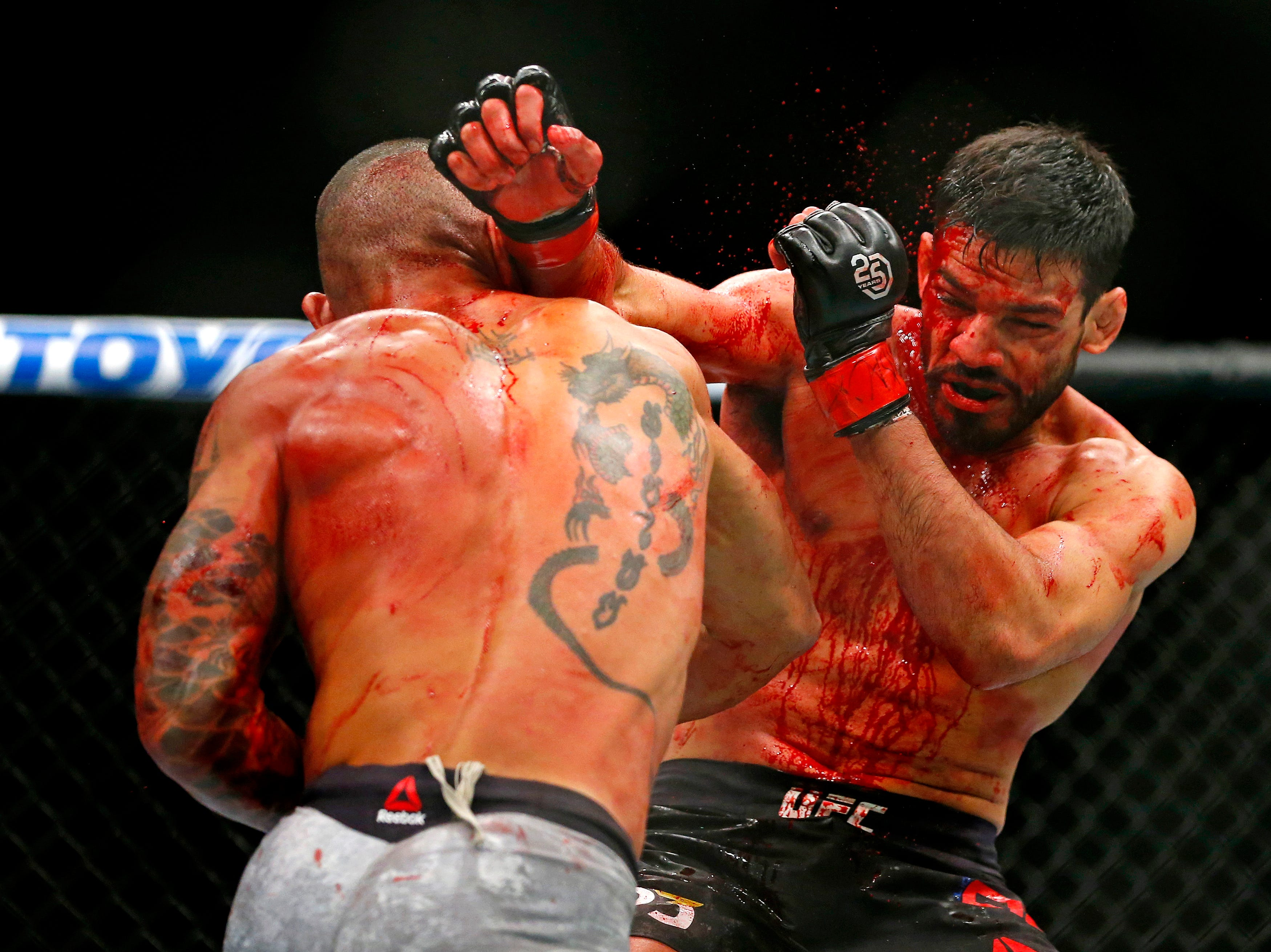 Julio Arce (red gloves) fights Sheymon Moreas (blue gloves) during UFC 230 at Madison Square Garden.