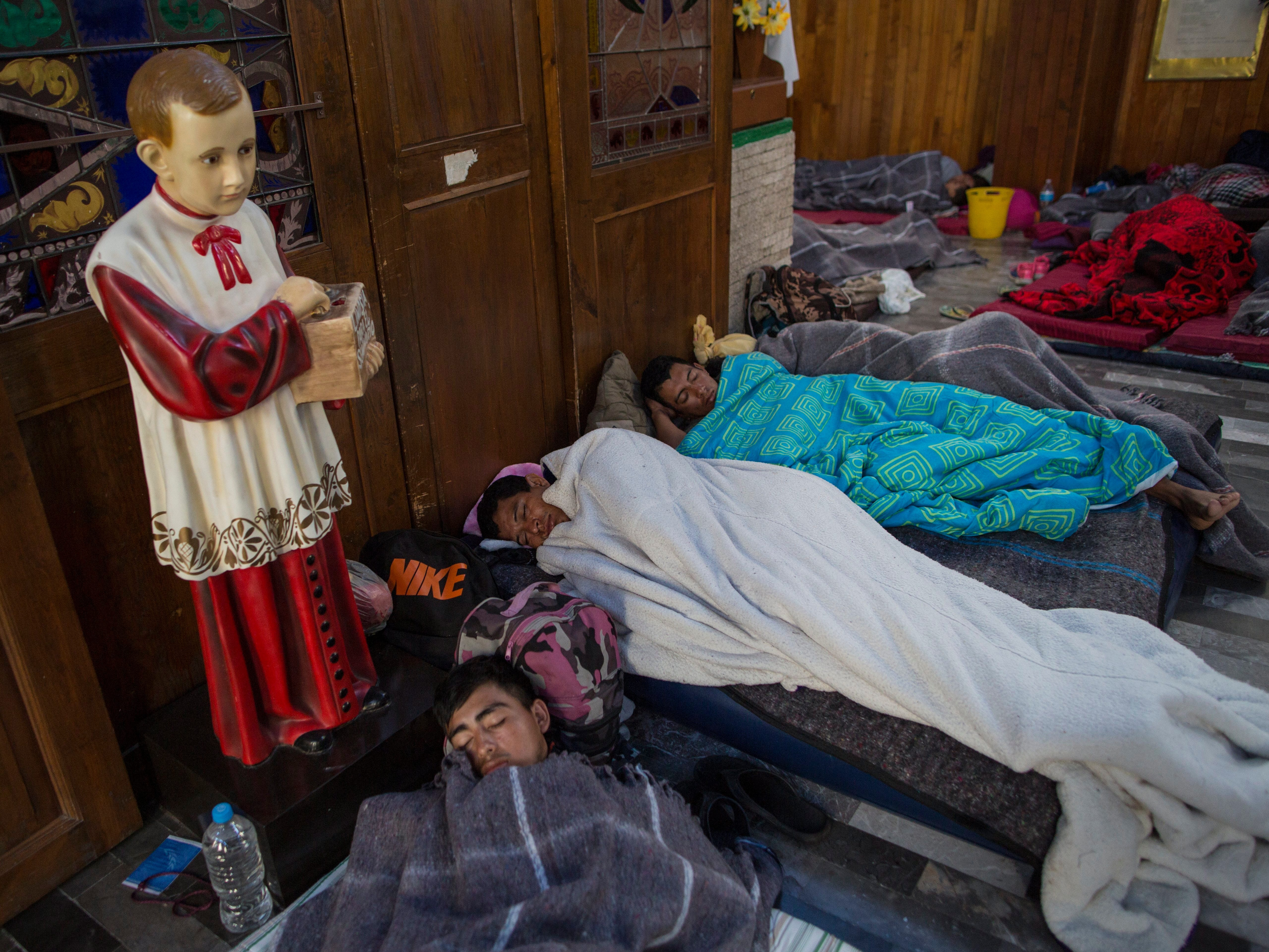 Central American migrants sleep inside a church that opened its doors to members of a caravan who splintered off the main group in order to reach the capital faster, in Puebla, Mexico, early Sunday, Nov. 4, 2018. Thousands of Central American migrants resumed their push toward the United States on Sunday, a day after arguments over the path ahead saw some travelers splinter away from the main caravan, which is entering a treacherous part of its journey through Mexico.