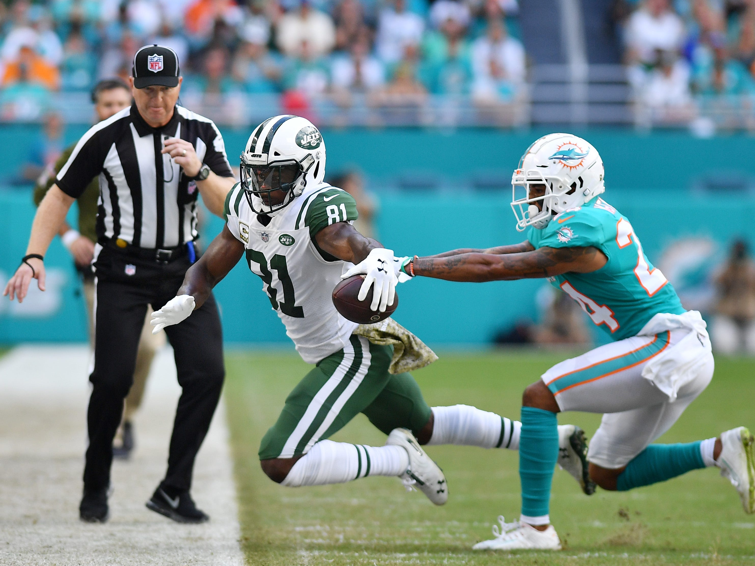 Quincy Enunwa (81) of the New York Jets tries to avoid the tackle of Torry McTyer (24) of the Miami Dolphins in the first half at Hard Rock Stadium.