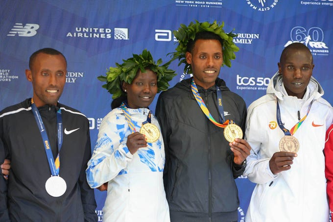 Men's winner Lelisa Desisa of Ethiopia (center) and women's winner Mary Keitany of Kenya pose during the medal ceremony with Shura Kitata of Ethiopia (left) and Geoffrey Kamworor of Kenya (far right) after  the New York City Marathon.