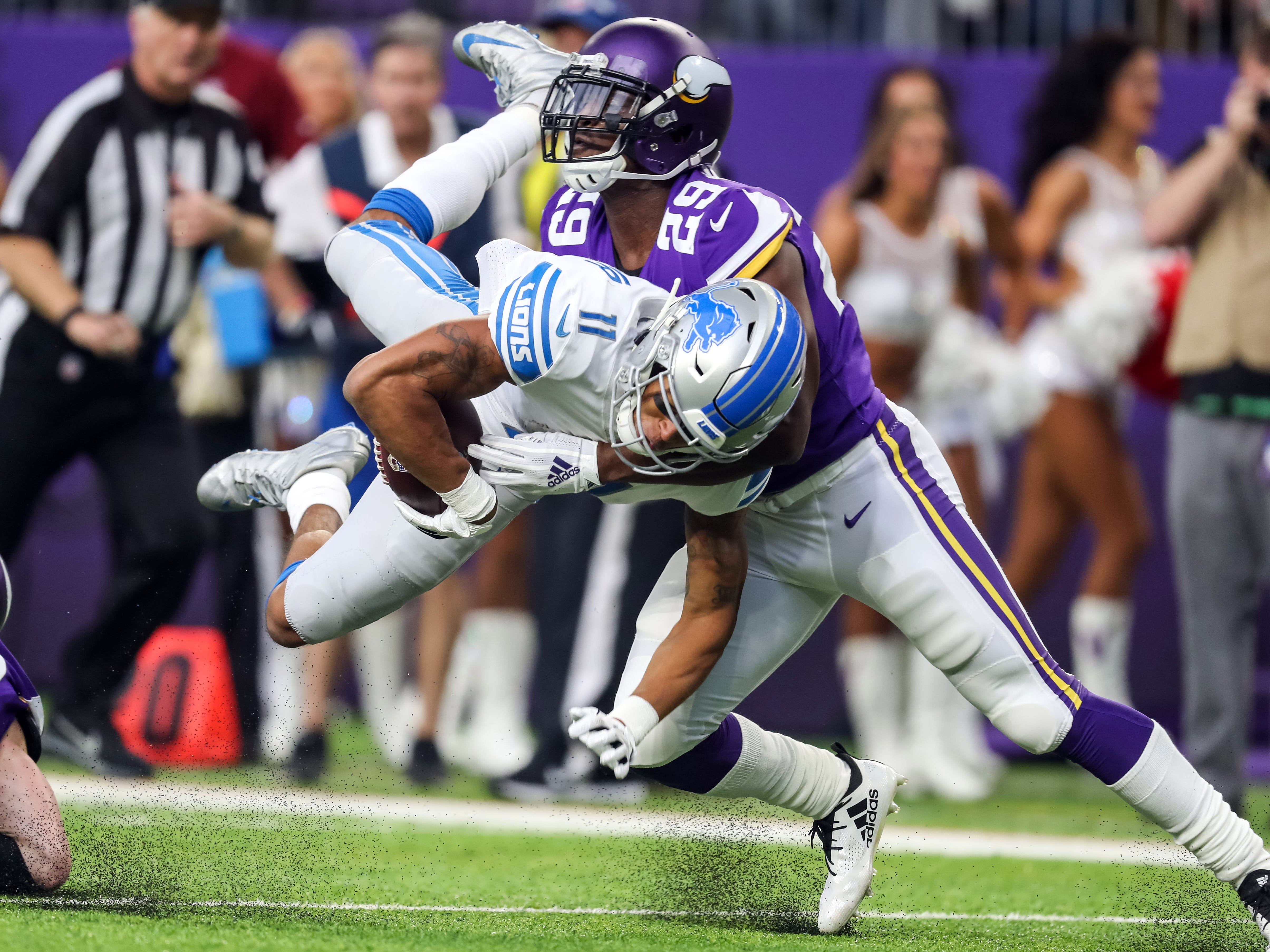 Minnesota Vikings cornerback Xavier Rhodes hits airborne Detroit Lions wide receiver Marvin Jones Jr. (11) during the first half at U.S. Bank Stadium.