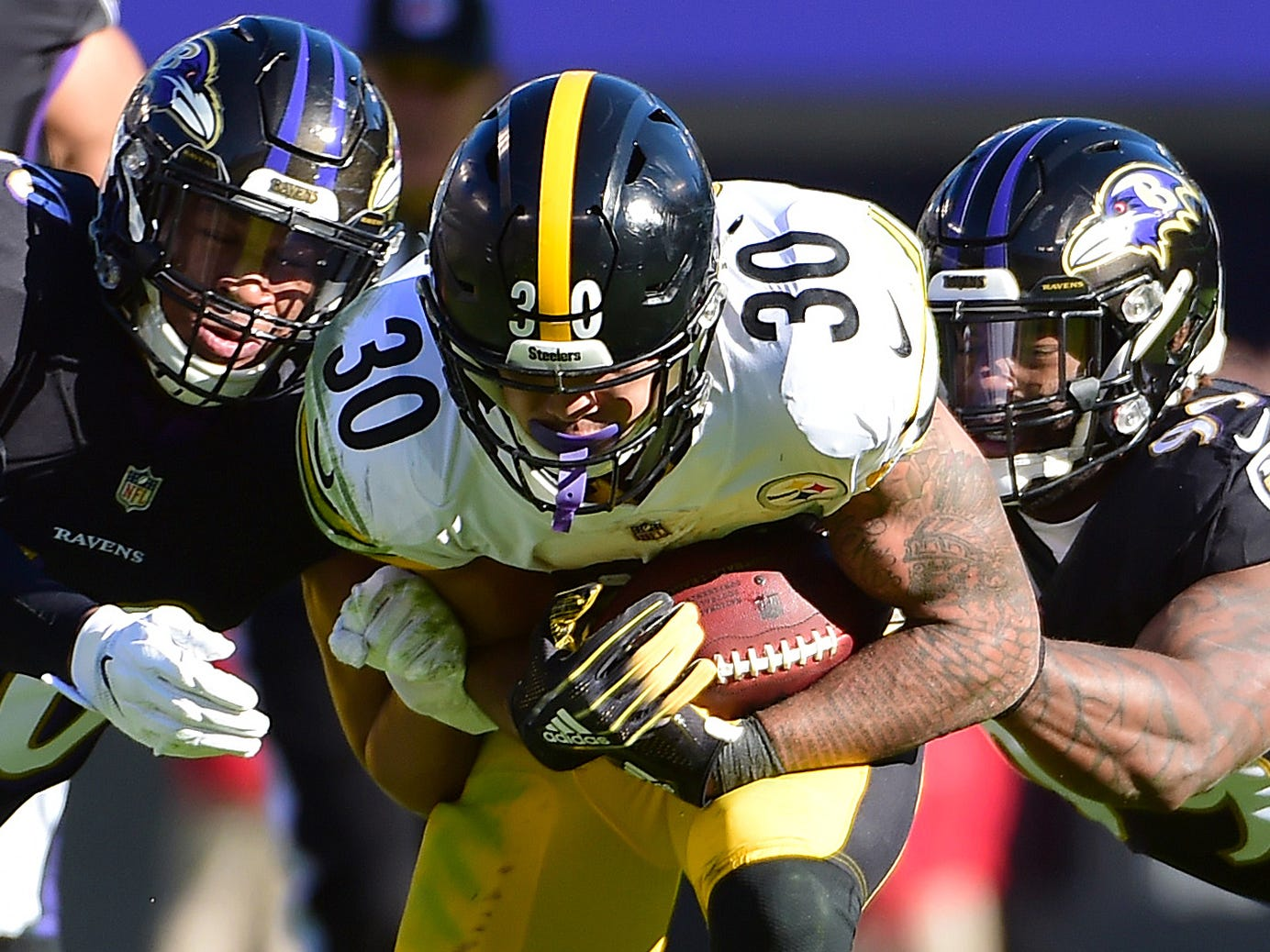 Baltimore Ravens linebackers Kenny Young (40) and Matthew Judon (99) wrap up Pittsburgh Steelers running back James Conner at M&T Bank Stadium.