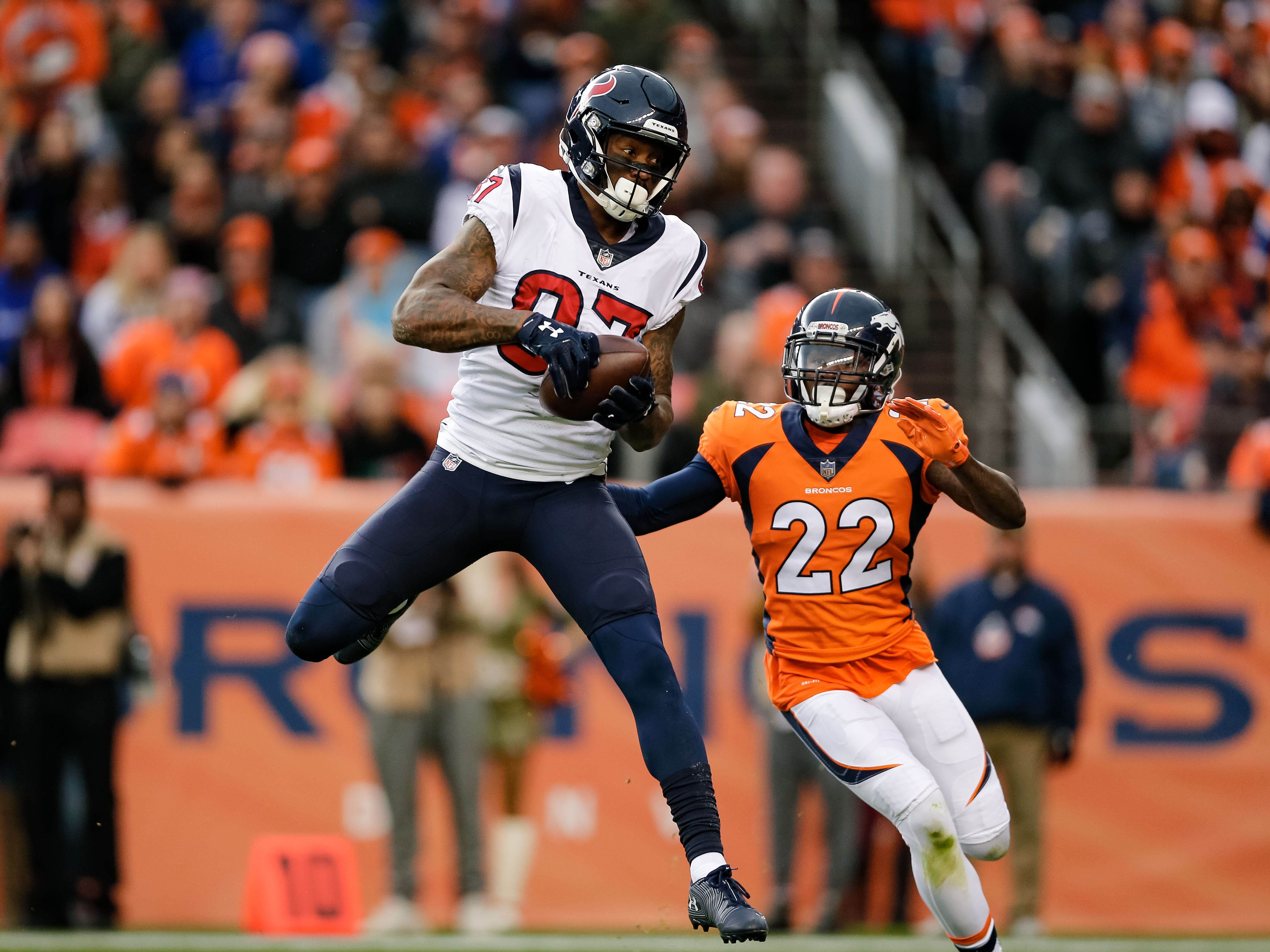 Houston Texans wide receiver Demaryius Thomas (87) makes a catch against Denver Broncos cornerback Tramaine Brock (22) in the first quarter at Broncos Stadium at Mile High.