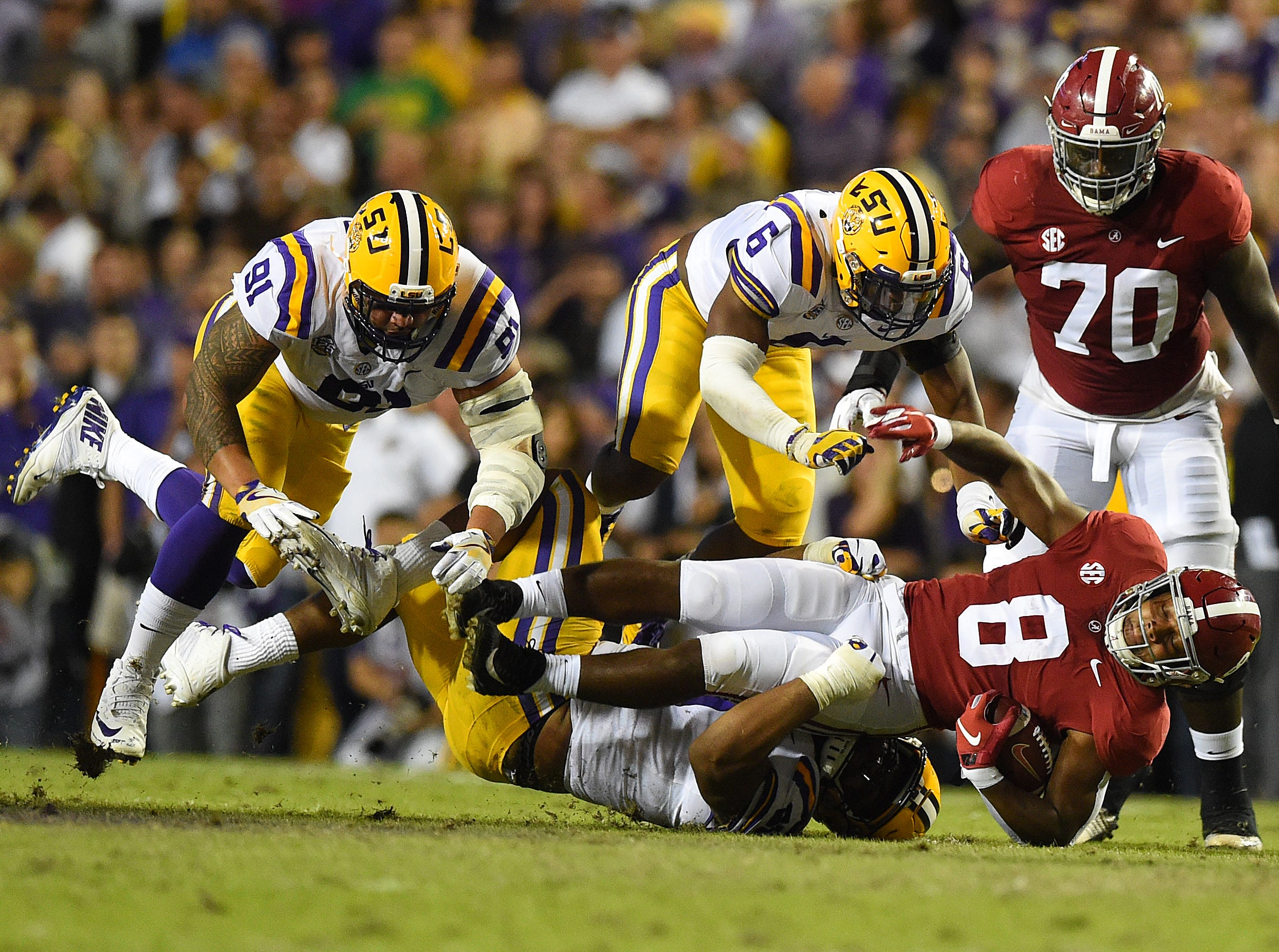 Alabama Crimson Tide running back Josh Jacobs (8) gets wrapped up by LSU Tigers defensive end Rashard Lawrence (90) on a carry during the first quarter at Tiger Stadium.