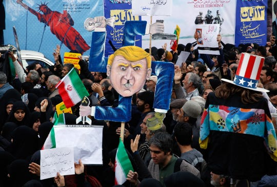 Iranians hold a placard showing a caricature of President Donald Trump during an anti-U.S. demonstration marking the 39th anniversary of the takeover of the U.S. Embassy.