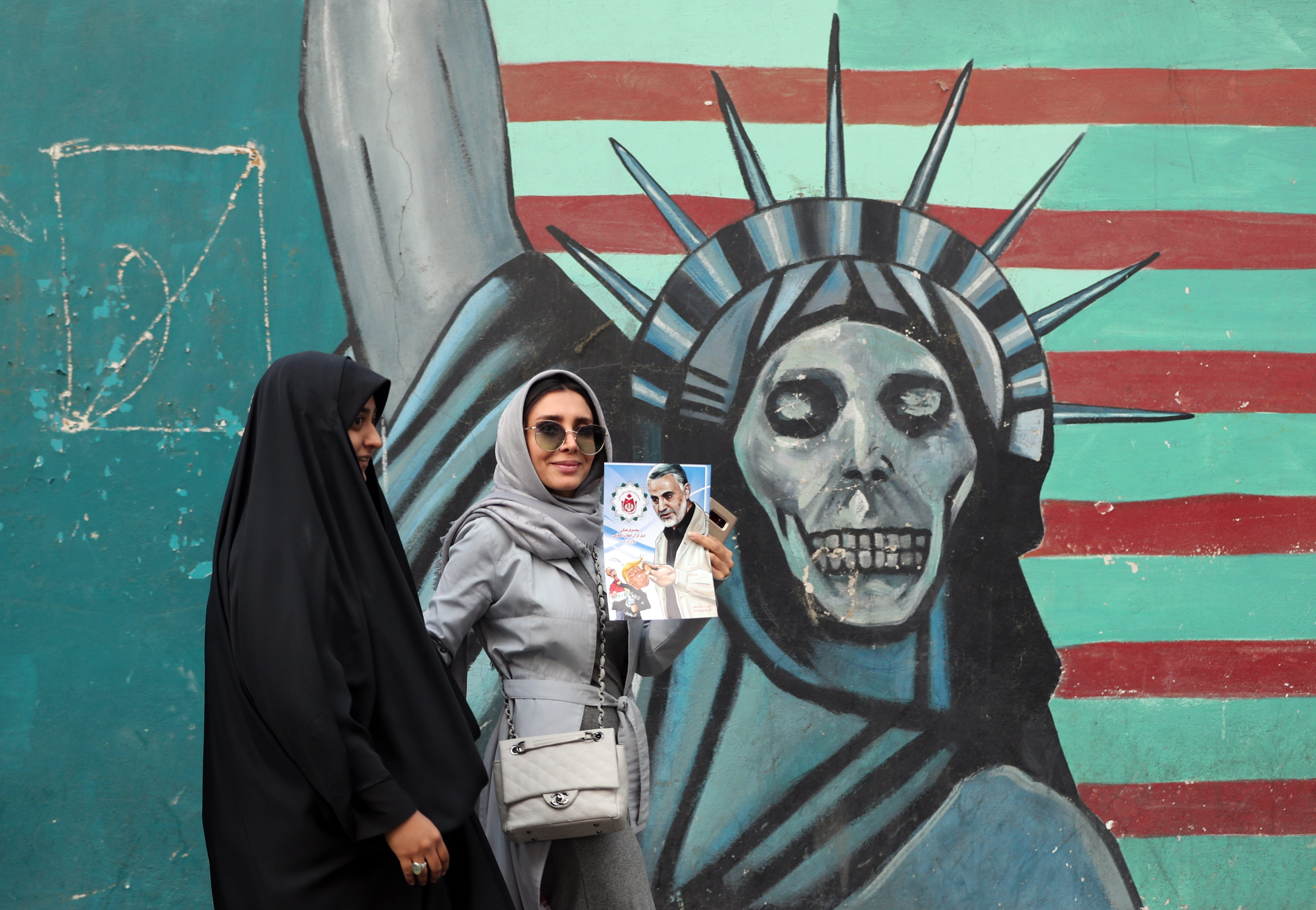 An Iranian woman holds a poster of an Iranian general from the Islamic Revolutionary Guard Corps as she walks past a mural depicting a skull-faced Statue of Liberty near the former U.S. Embassy in Tehran, Iran, on Sunday, Nov. 4, 2018.