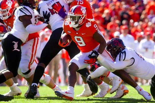 Clemson running back Travis Etienne  carries the ball during the first half against Louisville