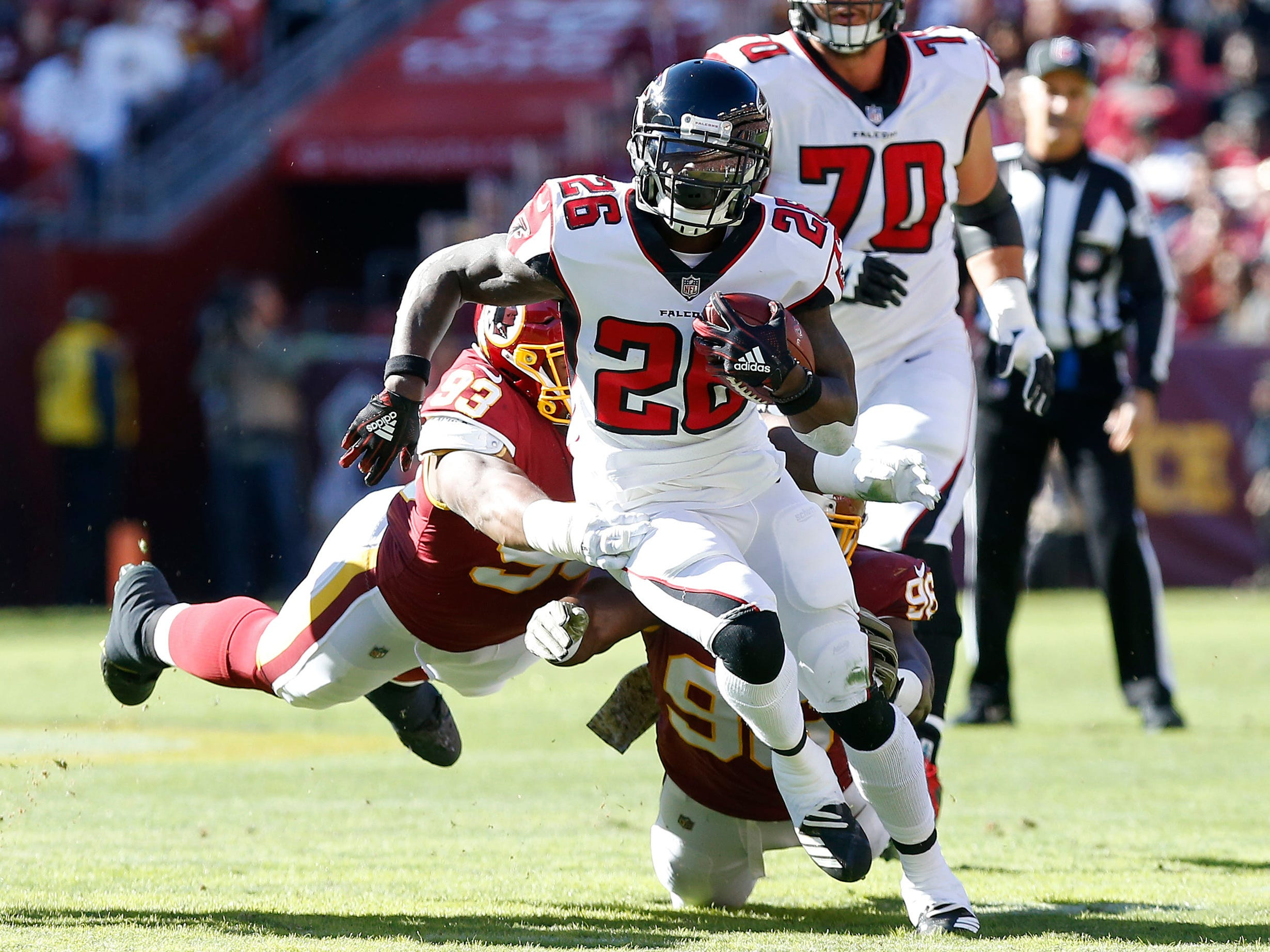 Atlanta Falcons running back Tevin Coleman (26) carries the ball past Washington Redskins defensive end Jonathan Allen (93) en route to a touchdown in the first quarter at FedExField.