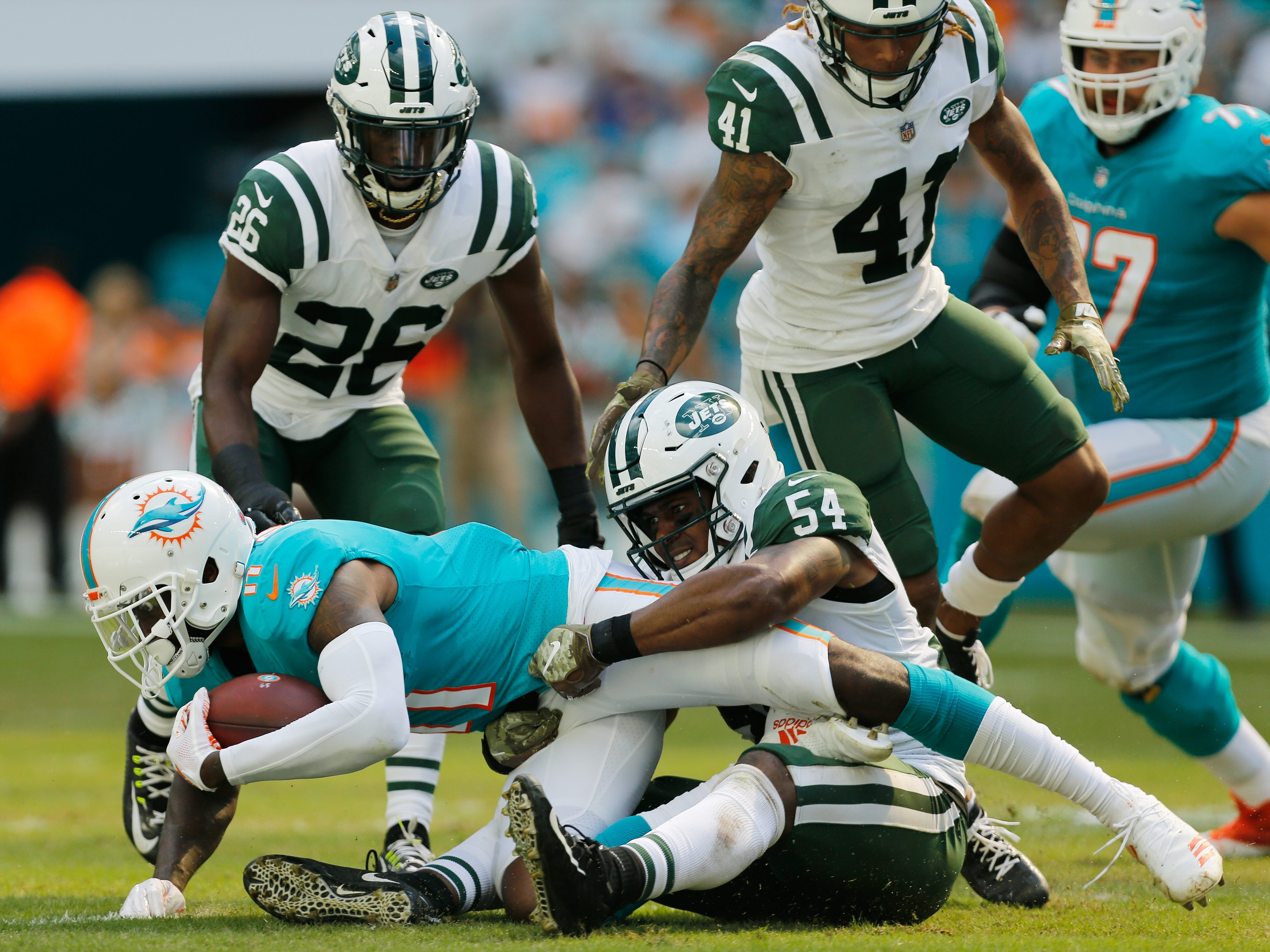 Avery Williamson (54) of the New York Jets tackles DeVante Parker (11) of the Miami Dolphins in the second quarter at Hard Rock Stadium.