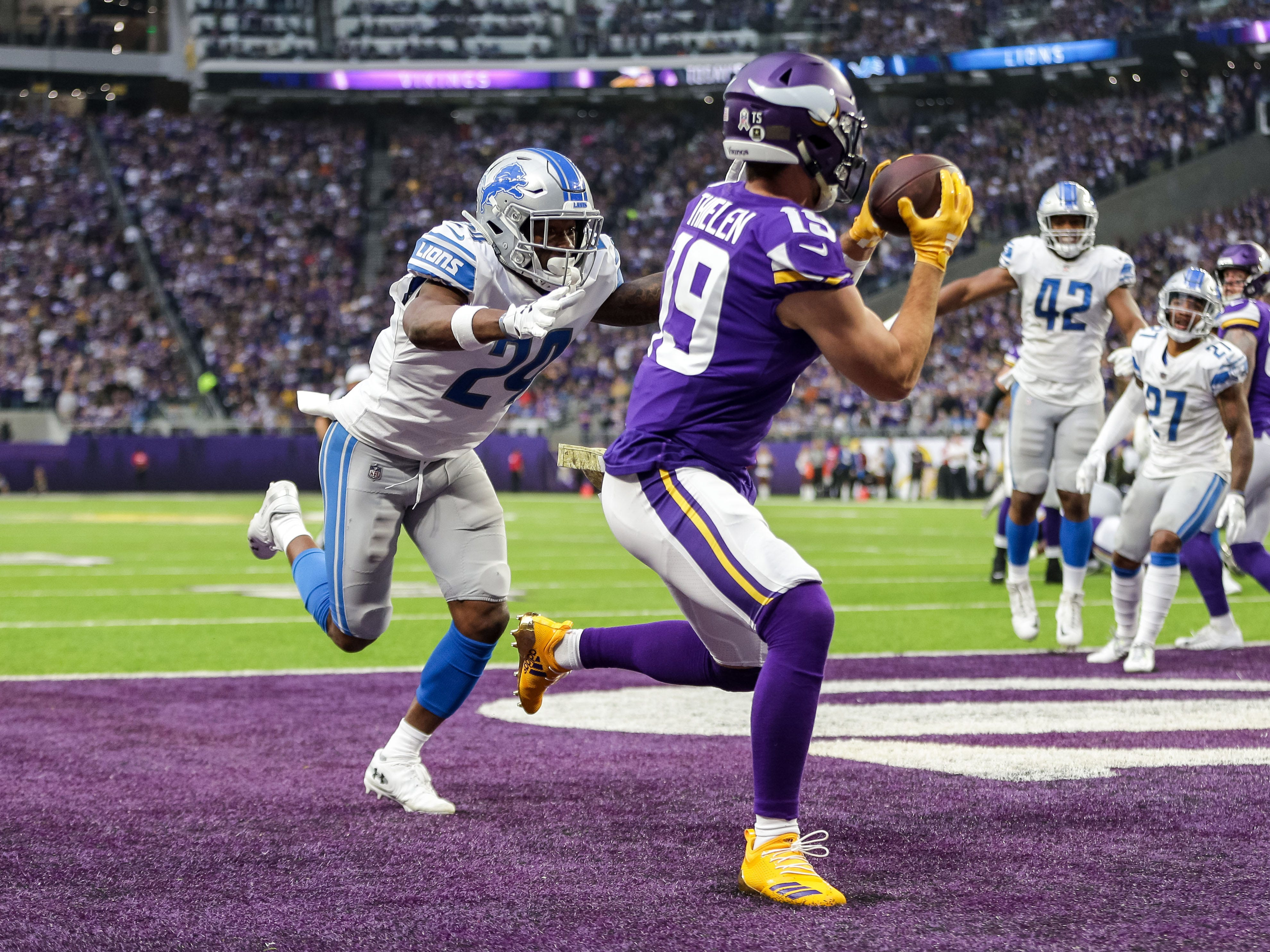 Minnesota Vikings wide receiver Adam Thielen (19) catches a touchdown pass in front of Detroit Lions cornerback Nevin Lawson (24) during the second quarter at U.S. Bank Stadium.