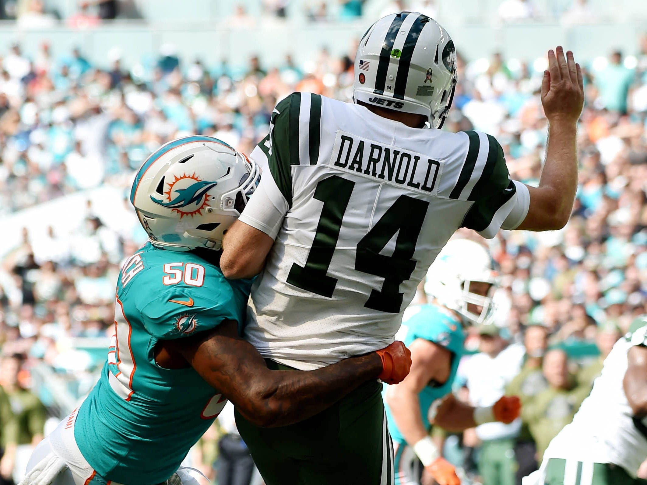 Miami Dolphins defensive end Andre Branch (50) hits New York Jets quarterback Sam Darnold (14) during the first half at Hard Rock Stadium.