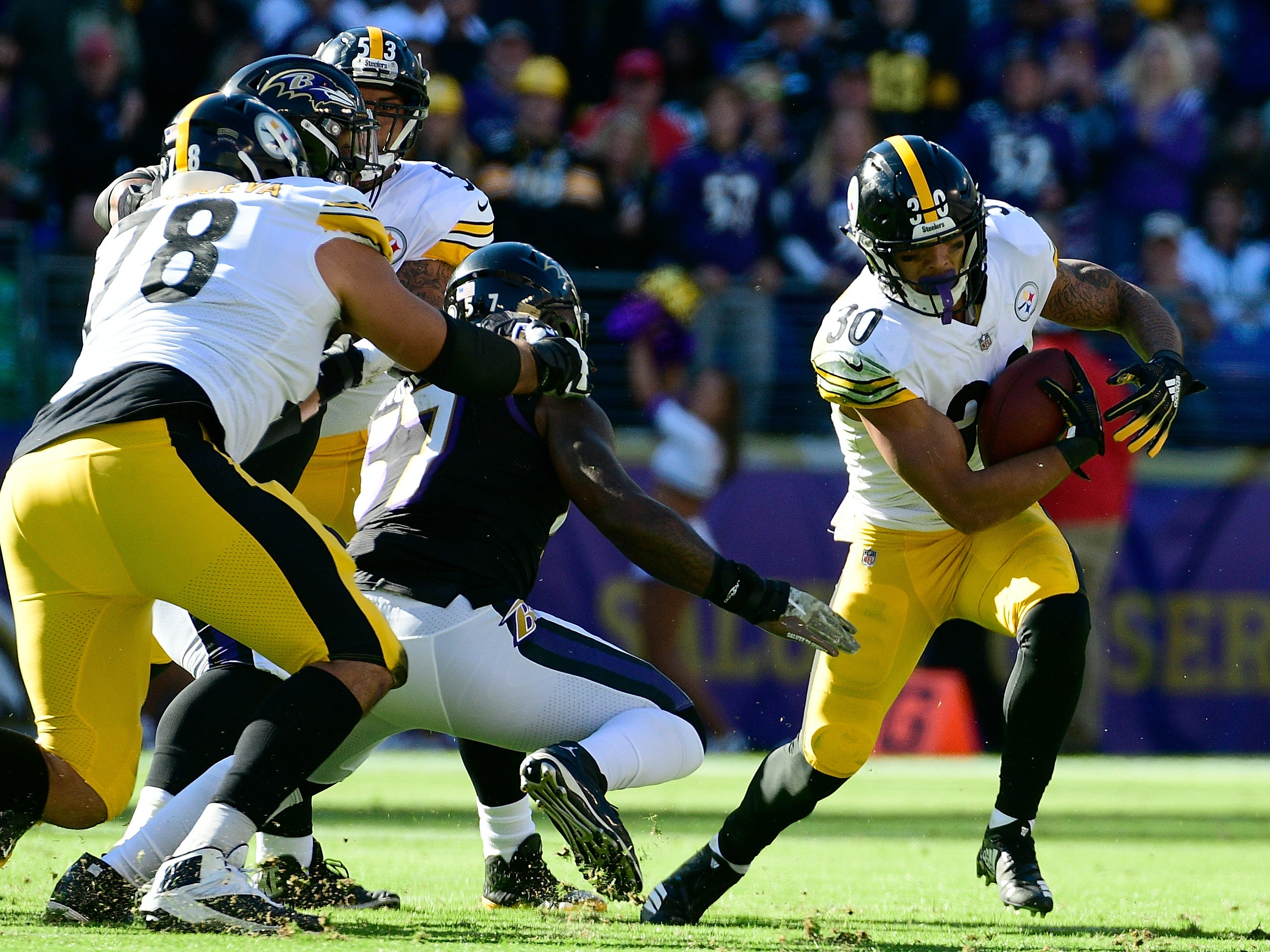 Pittsburgh Steelers running back James Conner (30) eludes a tackler during the first quarter against the Baltimore Ravens at M&T Bank Stadium.