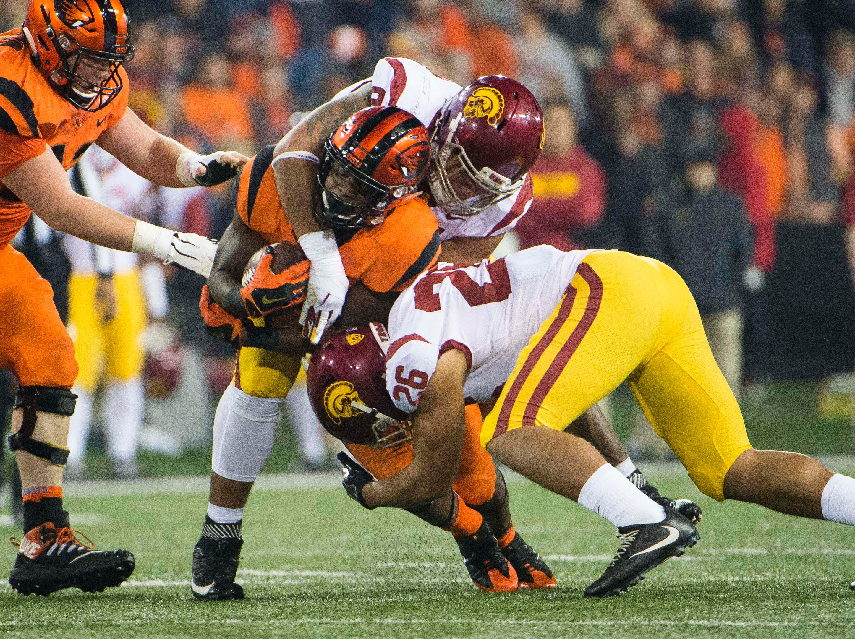 Oregon State Beavers running back Jermar Jefferson (22) is tackled by USC Trojans defensive lineman Brandon Pili (91) and linebacker Kana'i Mauga (26) during the second half at Reser Stadium.