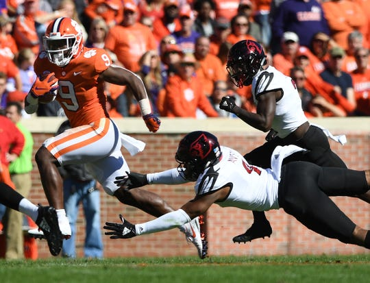 Clemson running back Travis Etienne (9) carries past Louisville linebacker C.J. Avery (9) during the 1st quarter Saturday, November 3, 2018 at Clemson's Memorial Stadium.