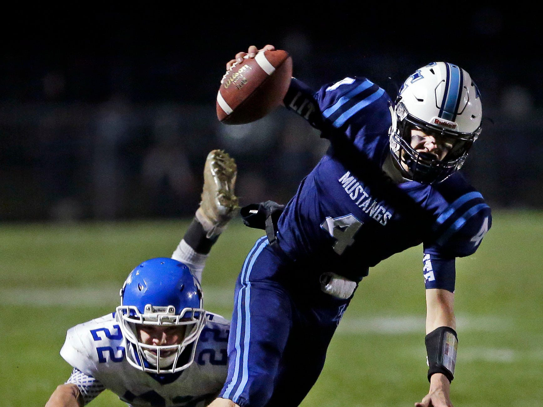 Quarterback Noah Mueller of Little Chute scrambles with the ball as he is tackled by Walker Vande Hey of Wrightstown in a WIAA Division 4 Level 3 playoff game Friday, November 2, 2018, at Fitzpatrick Field in Little Chute, Wis.