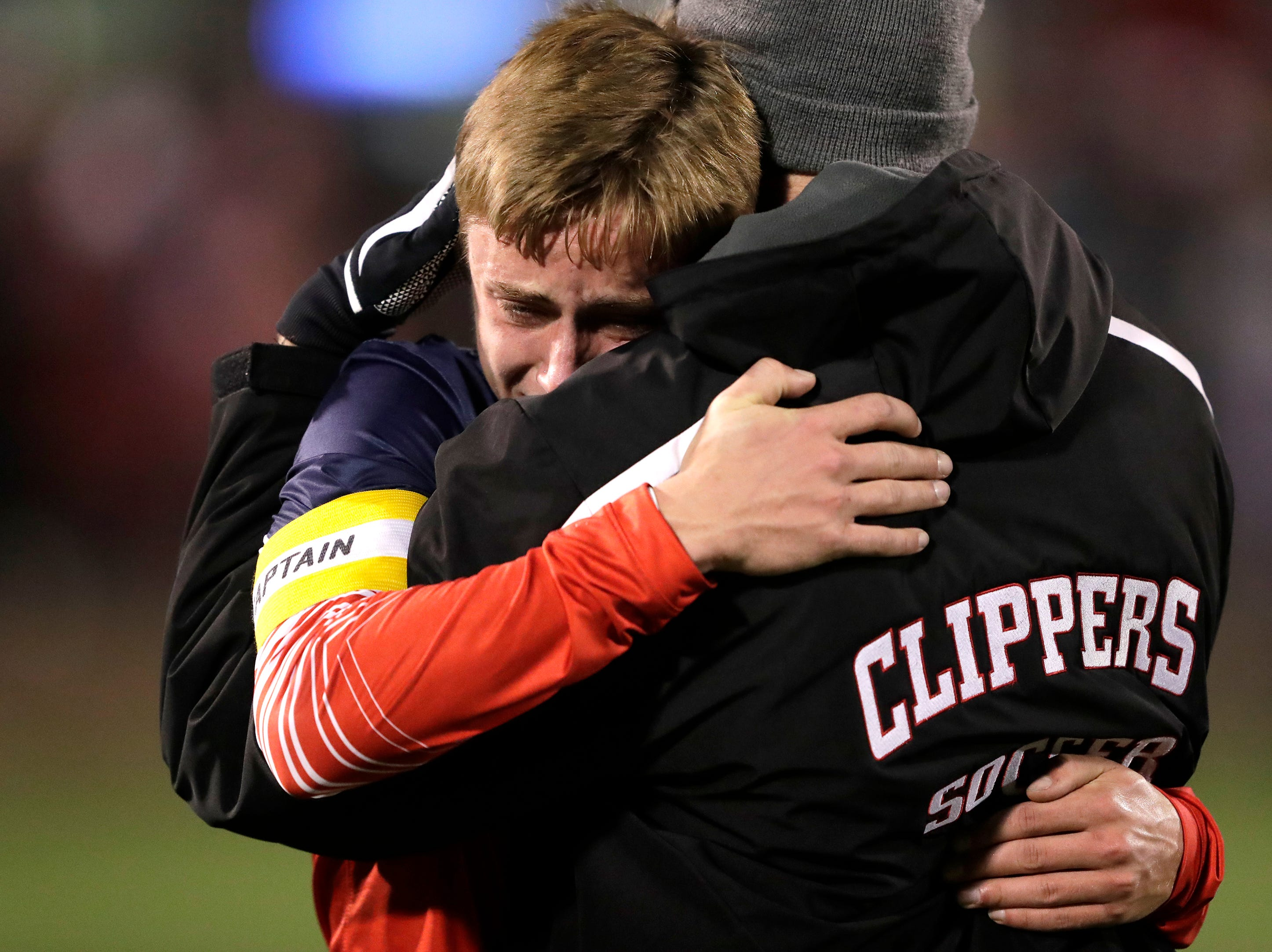 Sturgeon Bay High School's DJ Reichel gets a hug from assistant coach Matt  Broomhall after a 4-1 loss against University School of Milwaukee during their WIAA Division 4 state semifinal boys soccer game Friday, November 2, 2018, at Uihlein Soccer Park in Milwaukee, Wis. 
