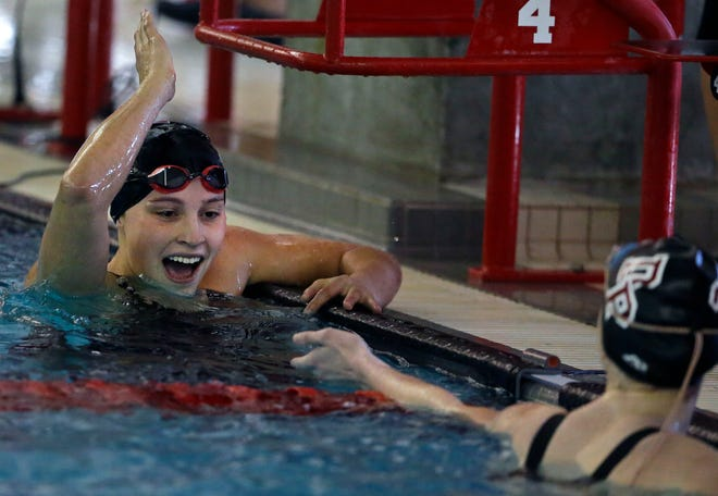 Claire Eisele of Neenah, left, and Lauren Finstad of De Pere/West De Pere share congratulations at the finish of the 100-yard freestyle event at the WIAA Division 1 swimming sectional meet in Neenah on Saturday.