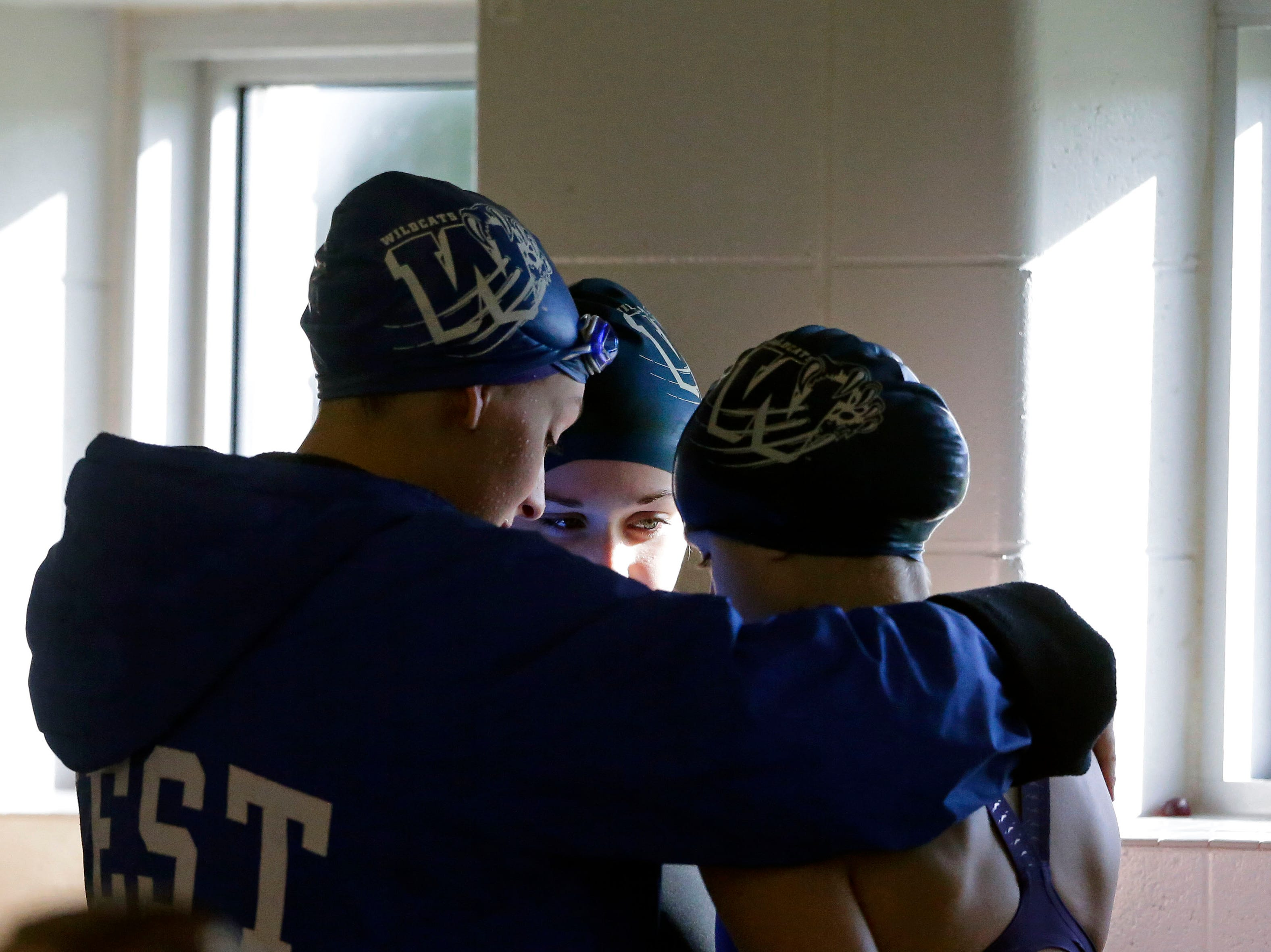 Oshkosh West swimmers huddle during the WIAA Division 1 swimming sectional meet Saturday, November 3, 2018, at Neenah High School in Neenah, Wis. Winners advanced to state.