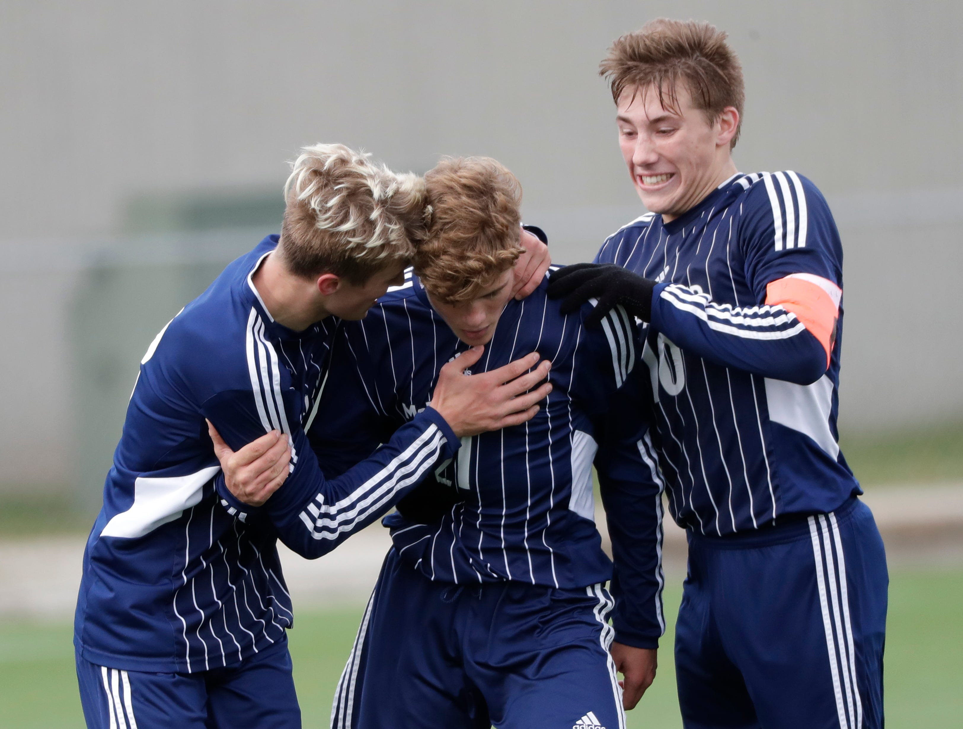 McFarland High School's Ethan Nichols, left, and Caleb Blair, right, congratulate Zach Nichols after he scored a goal against Plymouth High School during their WIAA Division 3 state semifinal boys soccer game Thursday, November 1, 2018, at Uihlein Soccer Park in Milwaukee, Wis. The goal gave McFarland a 2-0 lead with less than two minutes to play in the game.