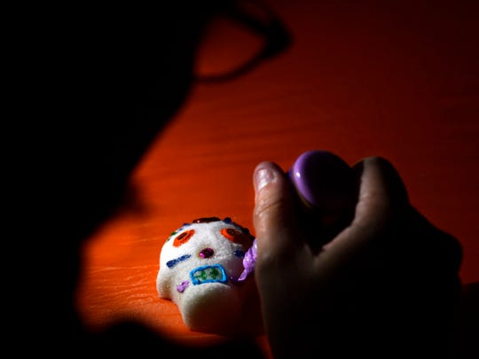 Mandi Lancaster decorates a sugar skull during Thursday's Dia de los Muertos Family Night in the garage next to the Grace Museum.
